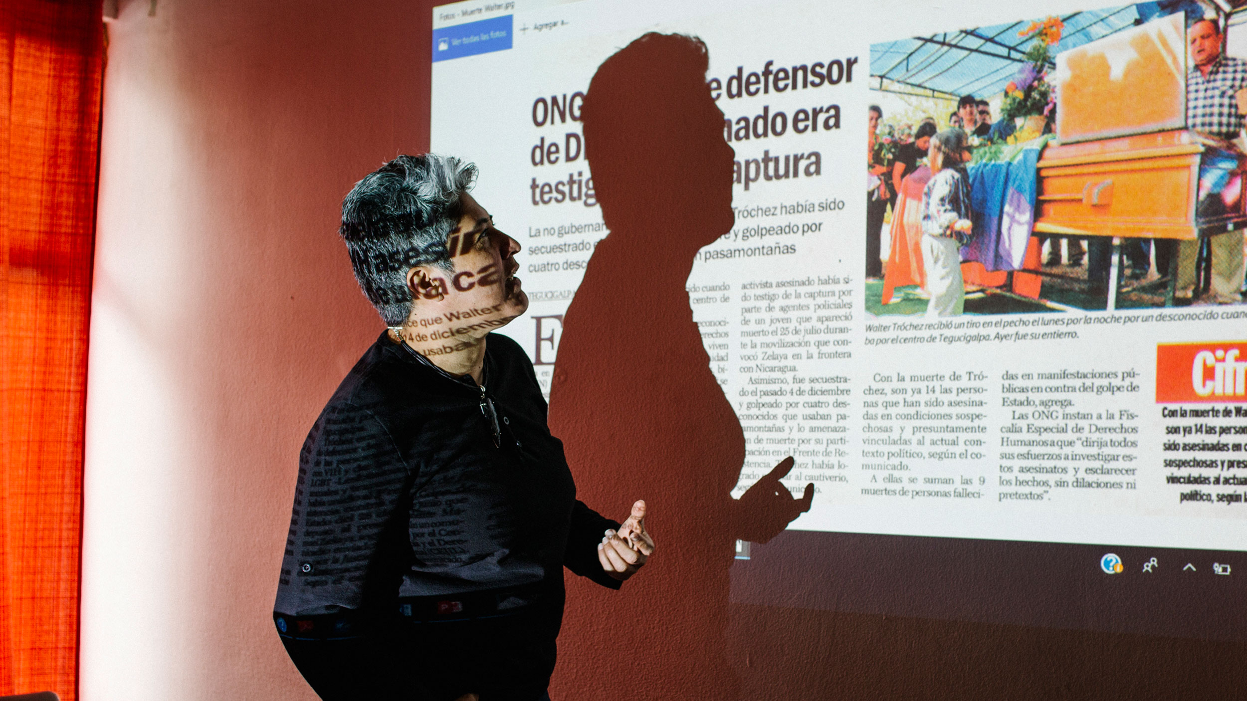 Indyra Mendoza is shown wearing a dark shirt and standing in front of a projector showing a news clipping.