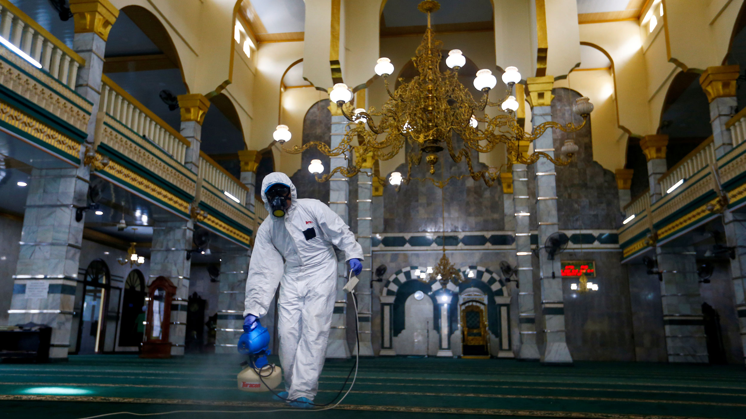 A medical officer wearing a white protective suit and a full face mask is shown spraying a carpet of a open area.