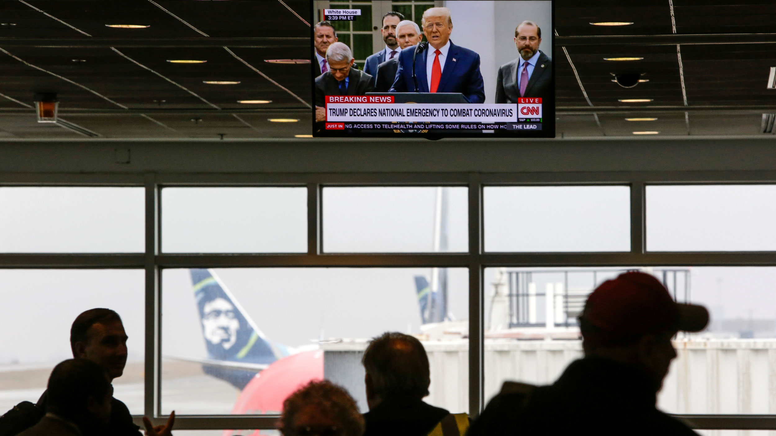 A television is shown hanging from the ceiling with US President Donald Trump displayed while several people are in shadow below.