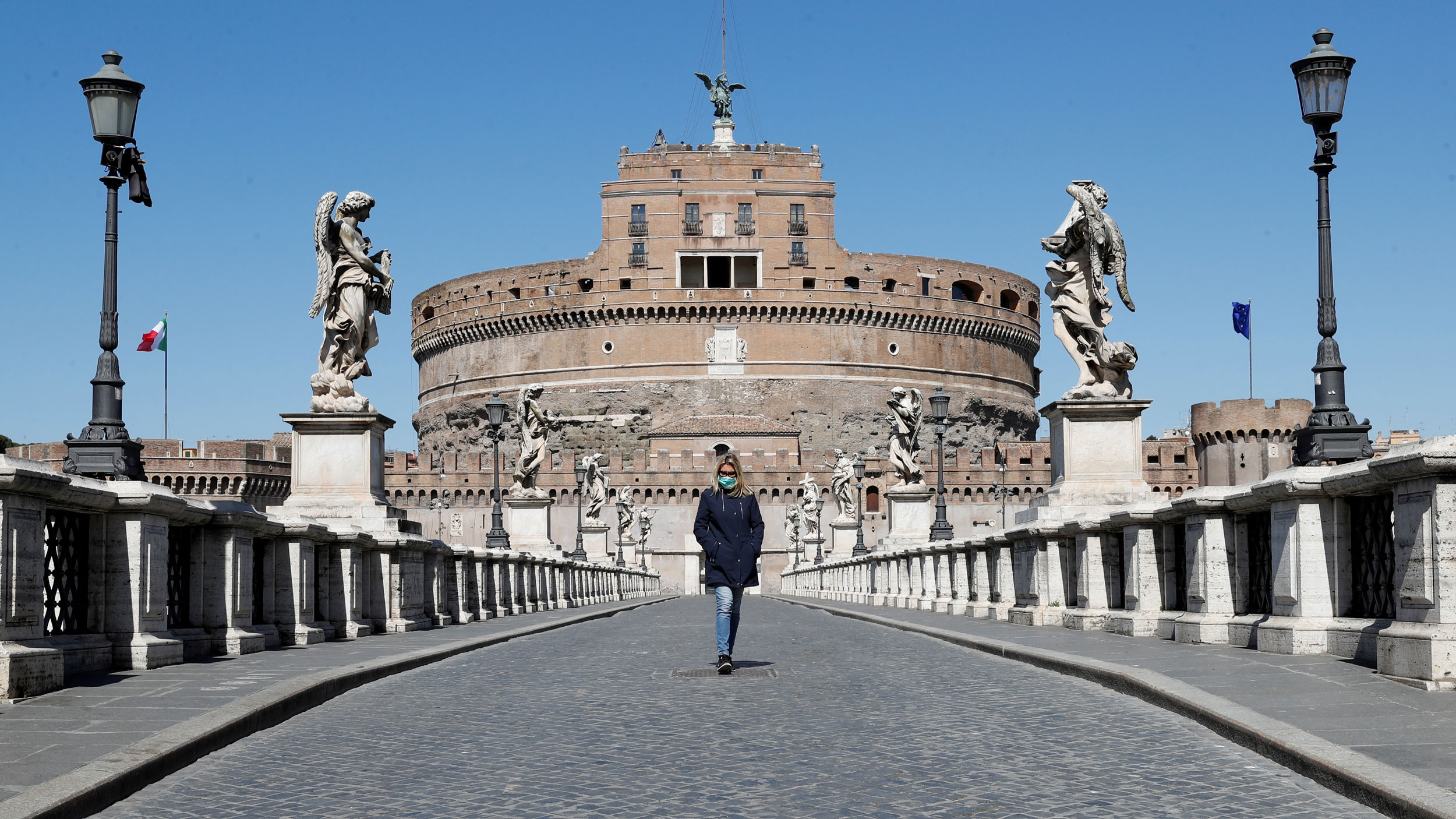 A woman wearing blue coat and a protective mask is shown walking on a bridge lined with stone statues outside Castel Sant'Angelo.