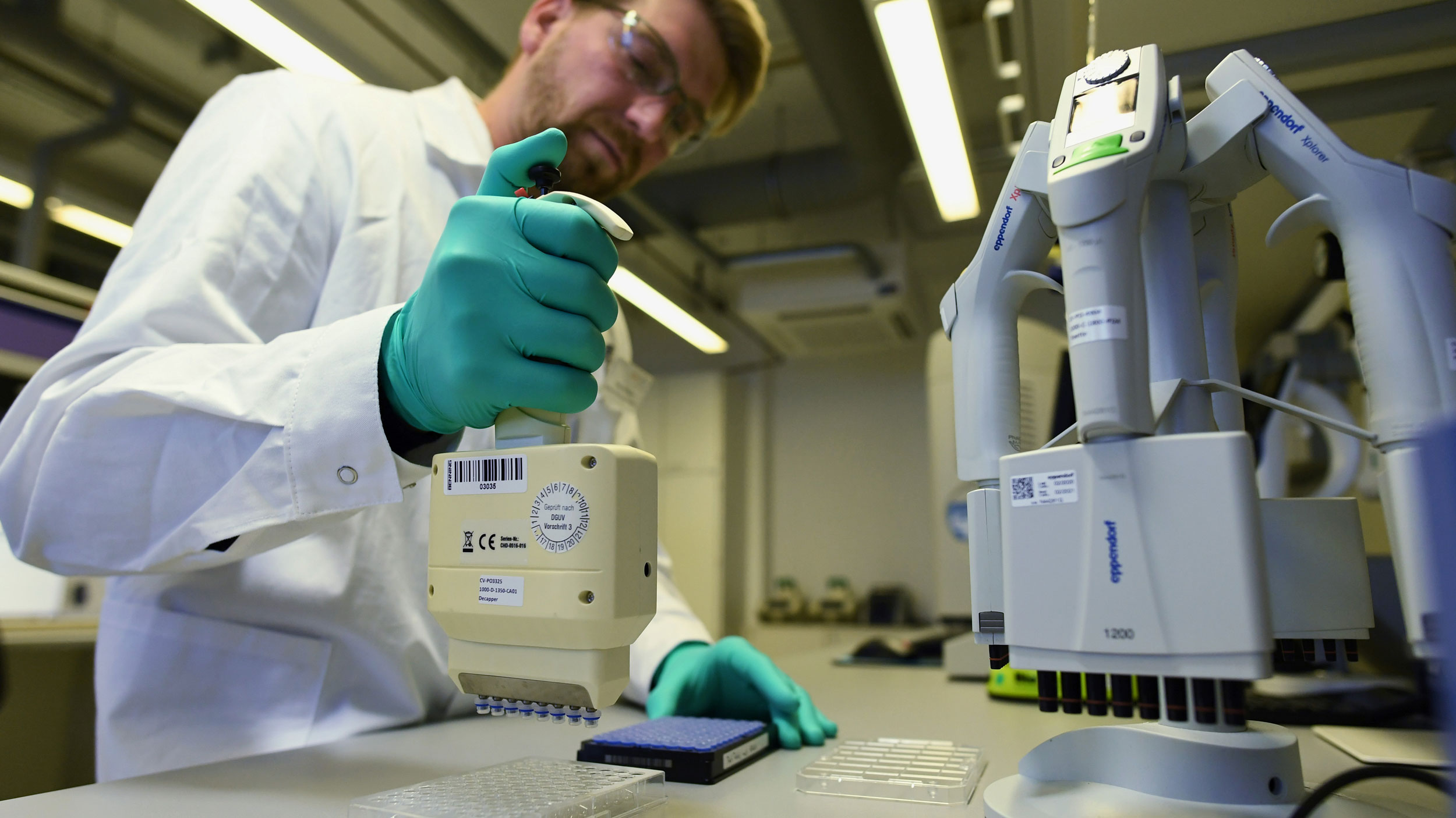 A biopharmaceutical researcher is shown wearing safety glasses, a white lab coat and protective gloves while conducting a test.
