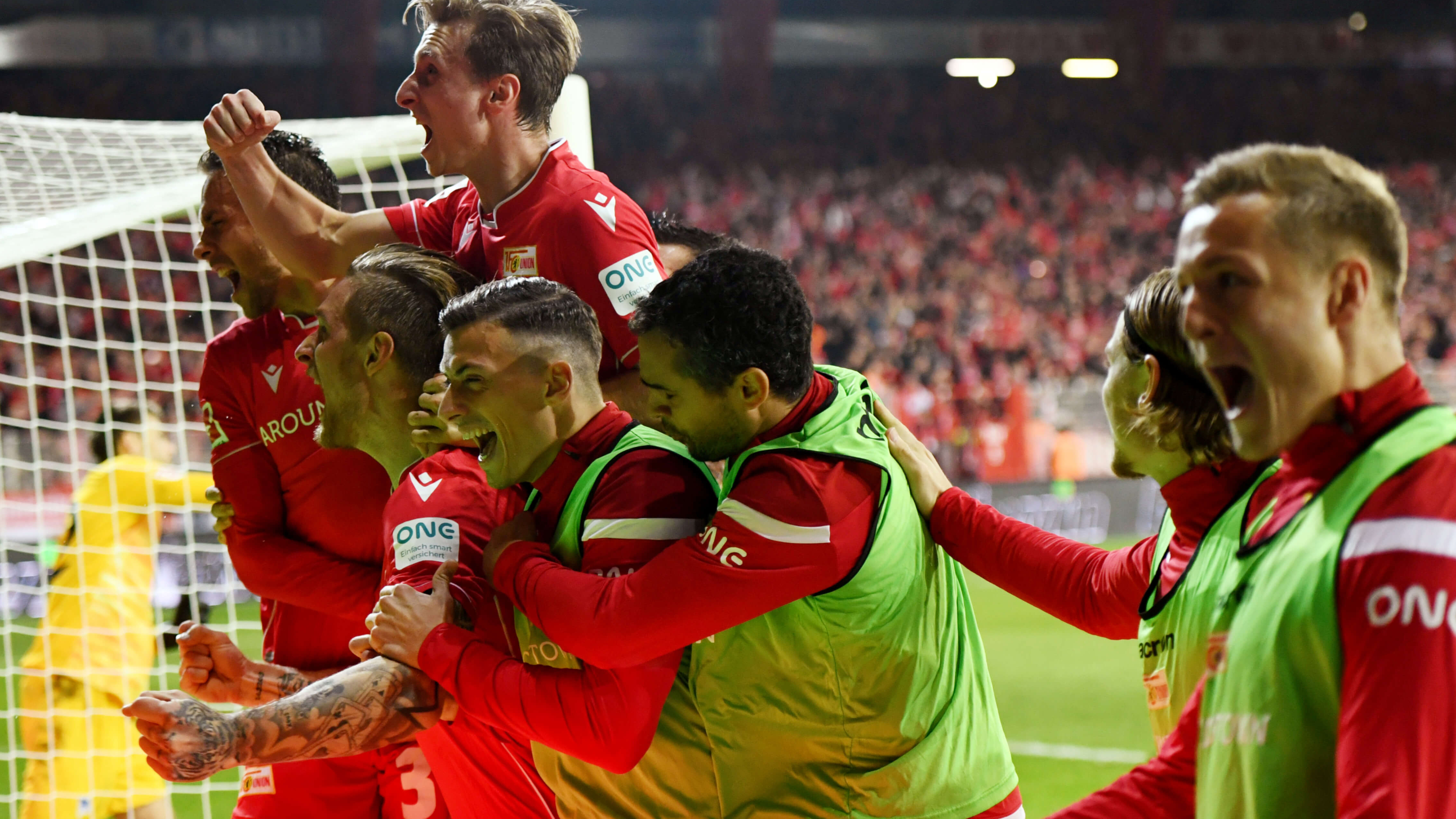 A group of men in red uniforms jump for joy on a soccer field.