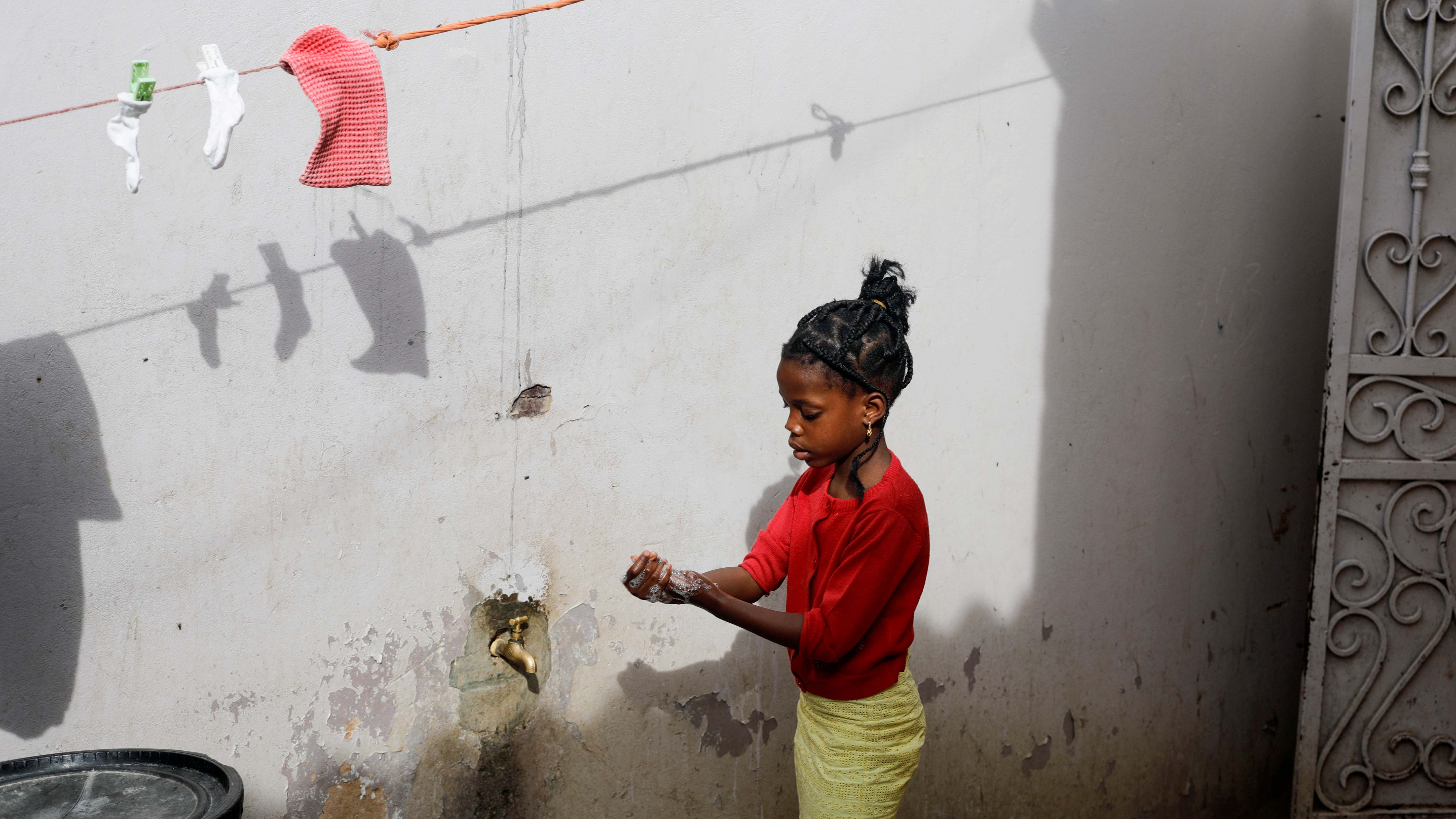 A girl washes her hands at a spigot at the entrance of her parents' house in Pikine, on the outskirts of Dakar, Senegal, on March 9, 2020.