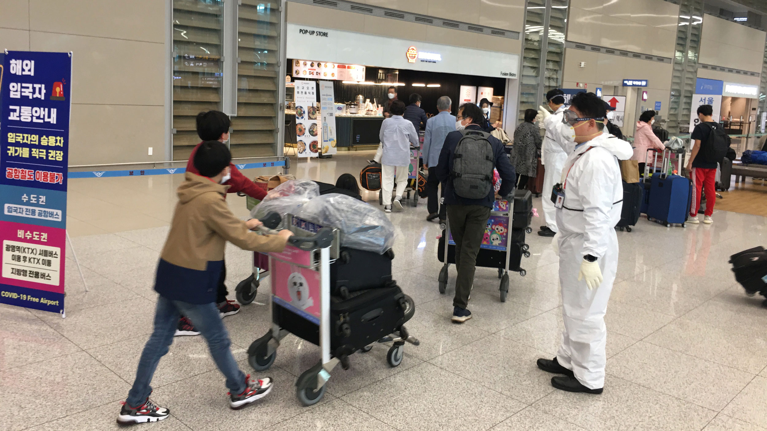 Arrivals at Incheon International Airport are directed by staff in protective gear.