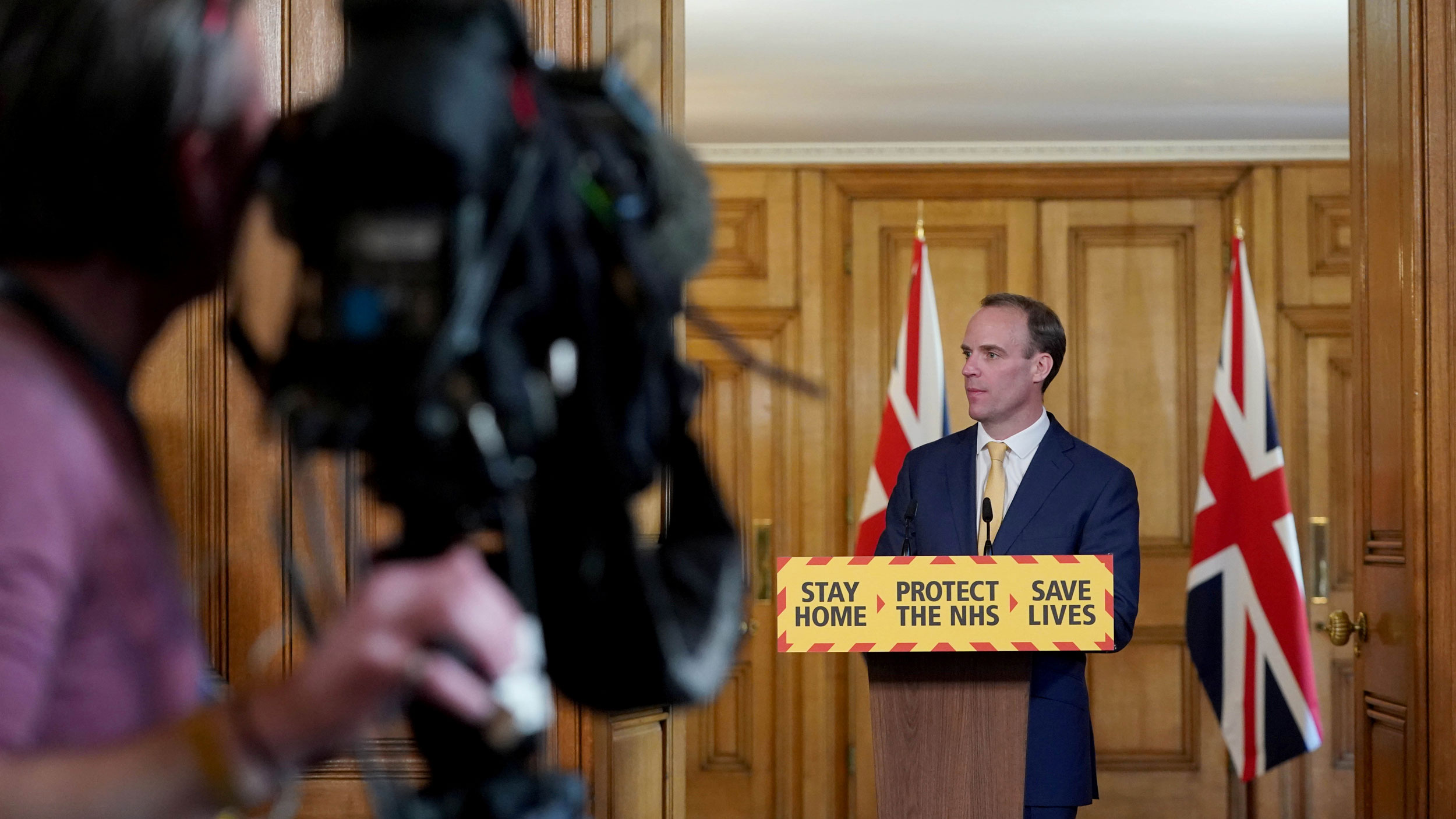 """Britain's Foreign Secretary Dominic Raab is shown standing behind a podium witth the words, """"Stay Home, Protect the NHS, Save Lives"""" printed on it."""