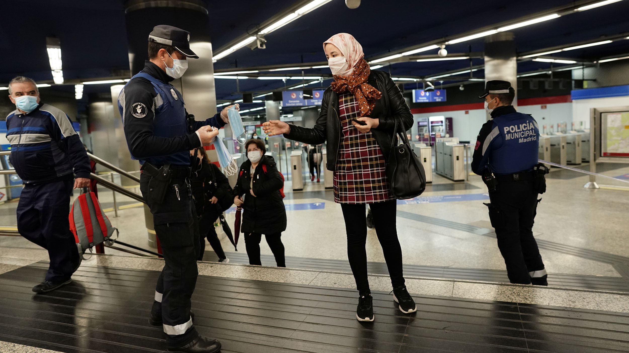 A police officer is shown holding several protective face masks and handing one out to a woman standing adjacent.