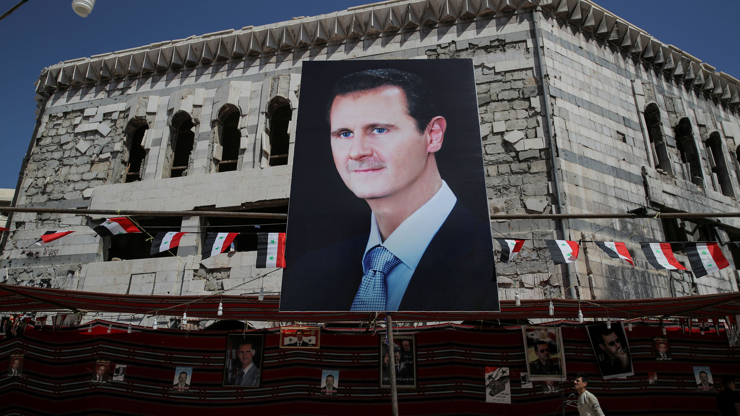 A large portrait photograph is show of Syrian president Bashar al-Assad with several Syrian flags flying behind it.