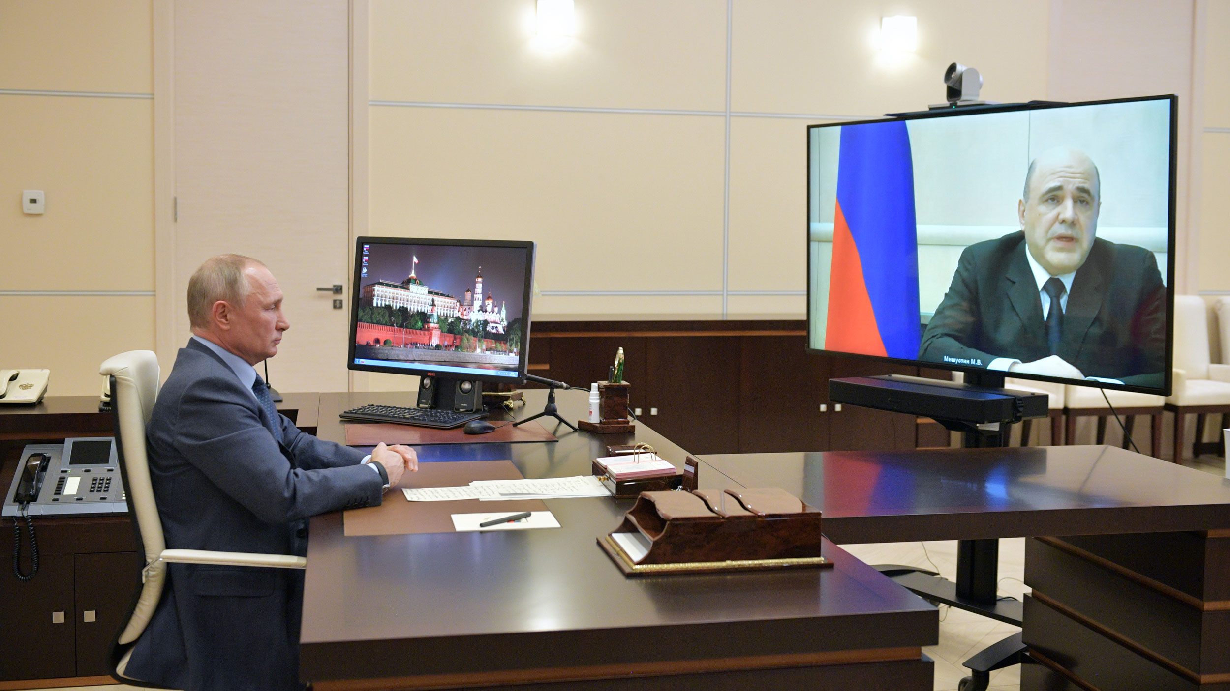 A man at a desk looks at a man on large screen