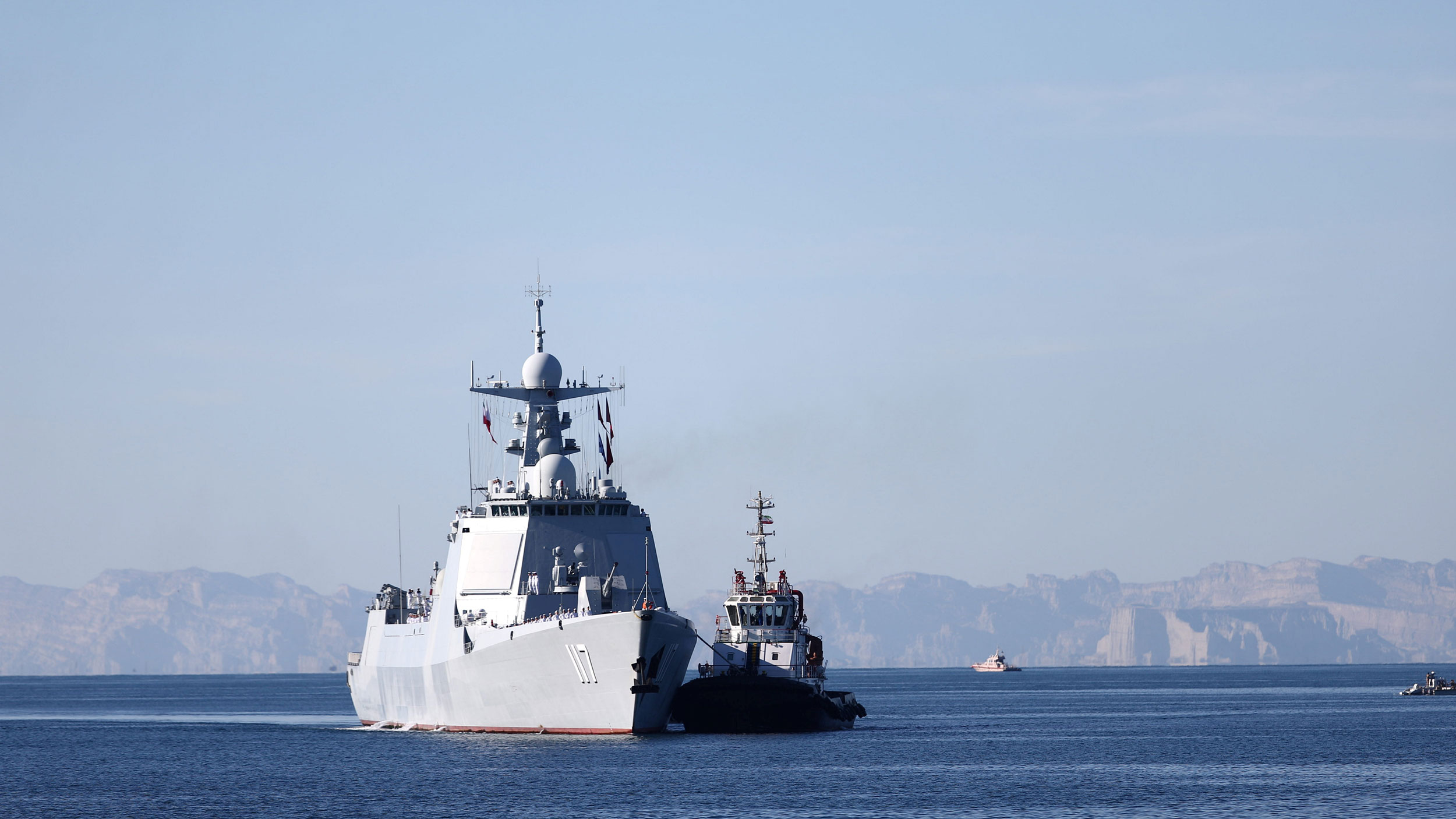 A warship sails in the Sea of Oman along side a smaller ship and a landmass shown in the distance.