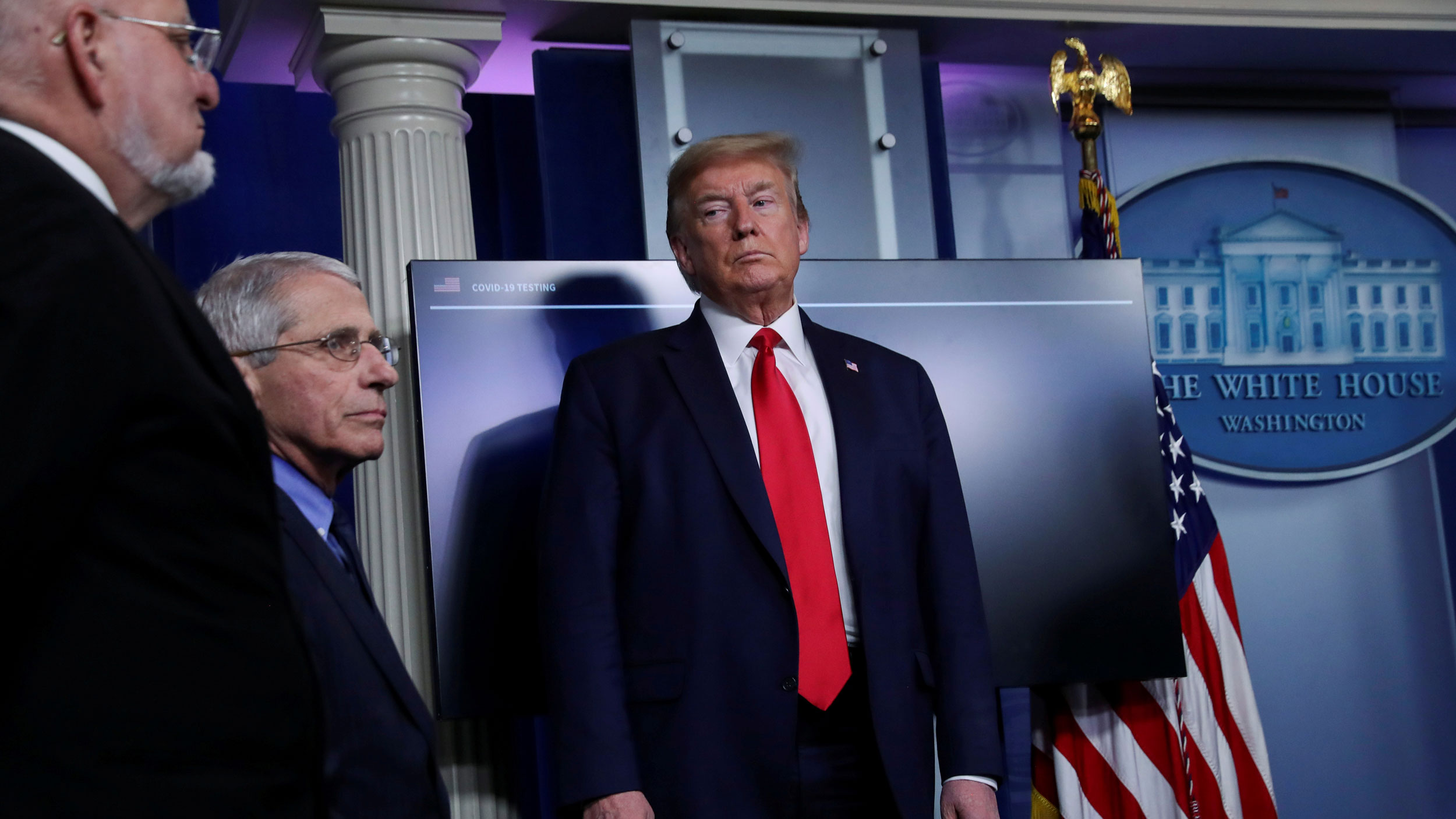 US President Donald Trump is shown wearing a dark suit and red tie and looking to his right at National Institute of Allergy and Infectious Diseases Director Dr. Anthony Fauci.