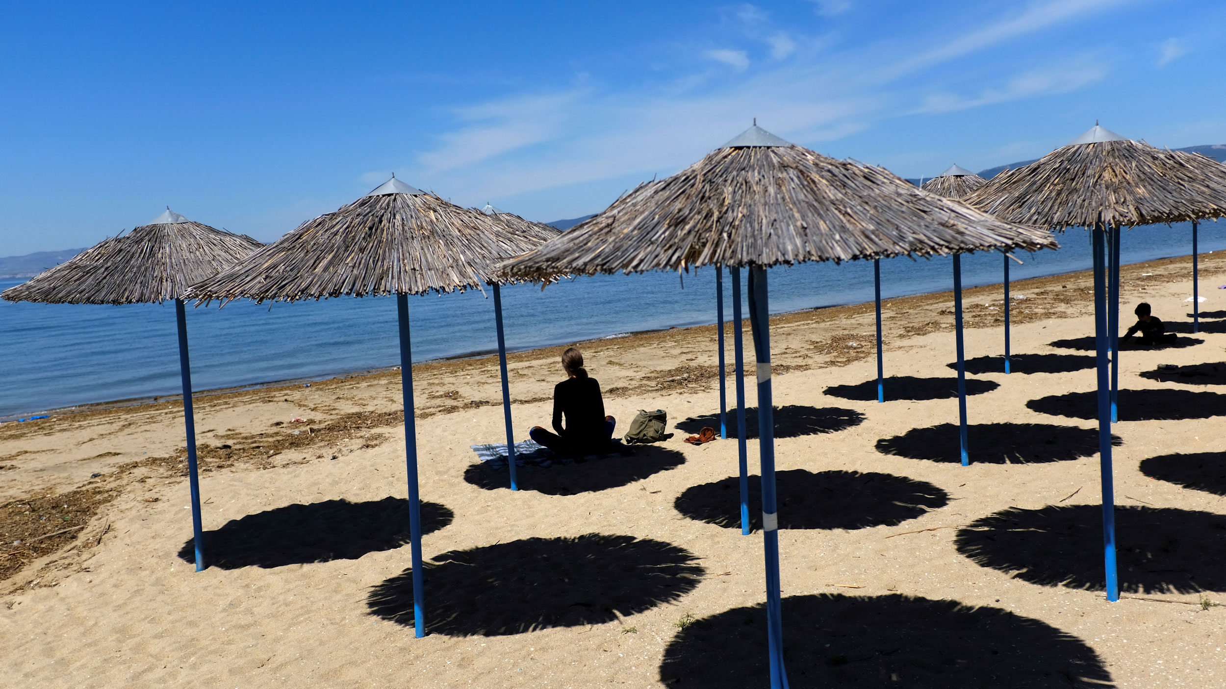 Several rows of thatch umbrellas are shown on a sandy beach with a woman in shadow sitting underneath one of the umbrellas.