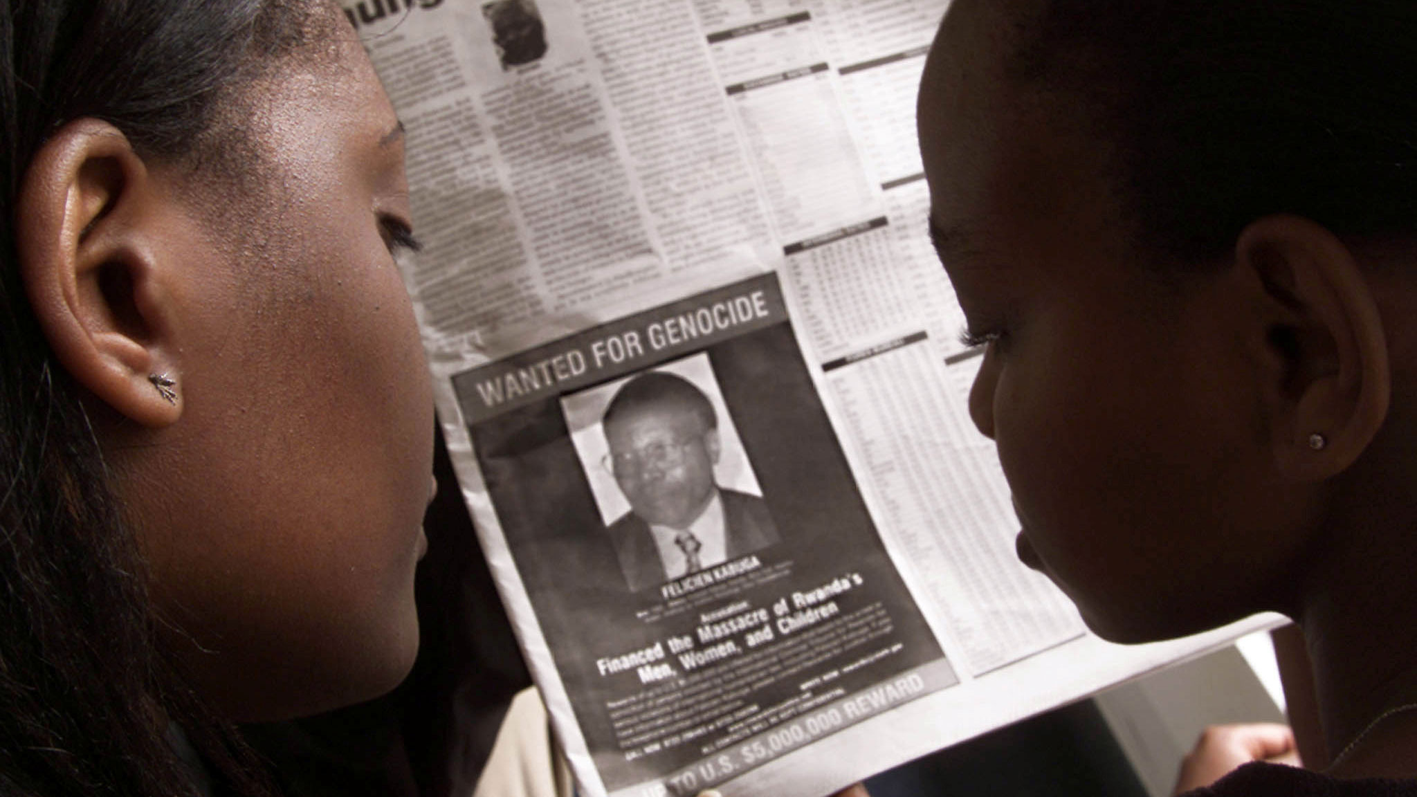 Two people are shown from behind looking at a newspaper featuring a photograph of Rwandan Felicien Kabuga.