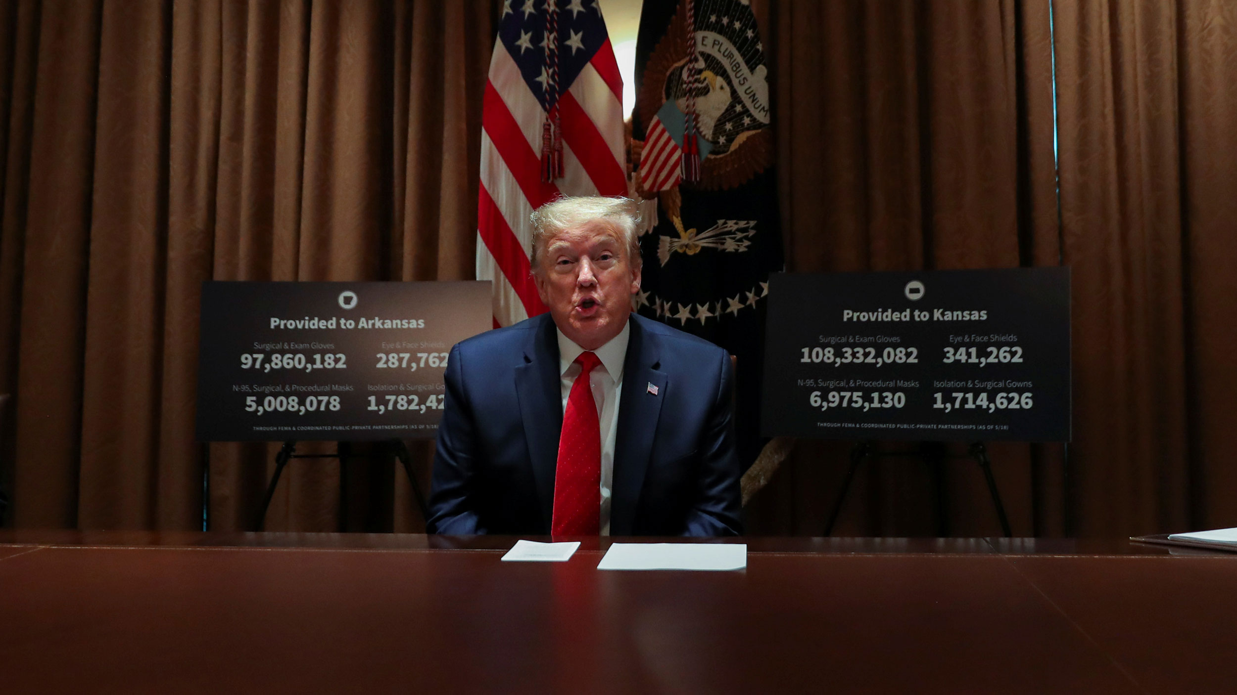 US President Donald Trump is shown sitting at a table wearing a dark suit and red tied with the US flag behind him.