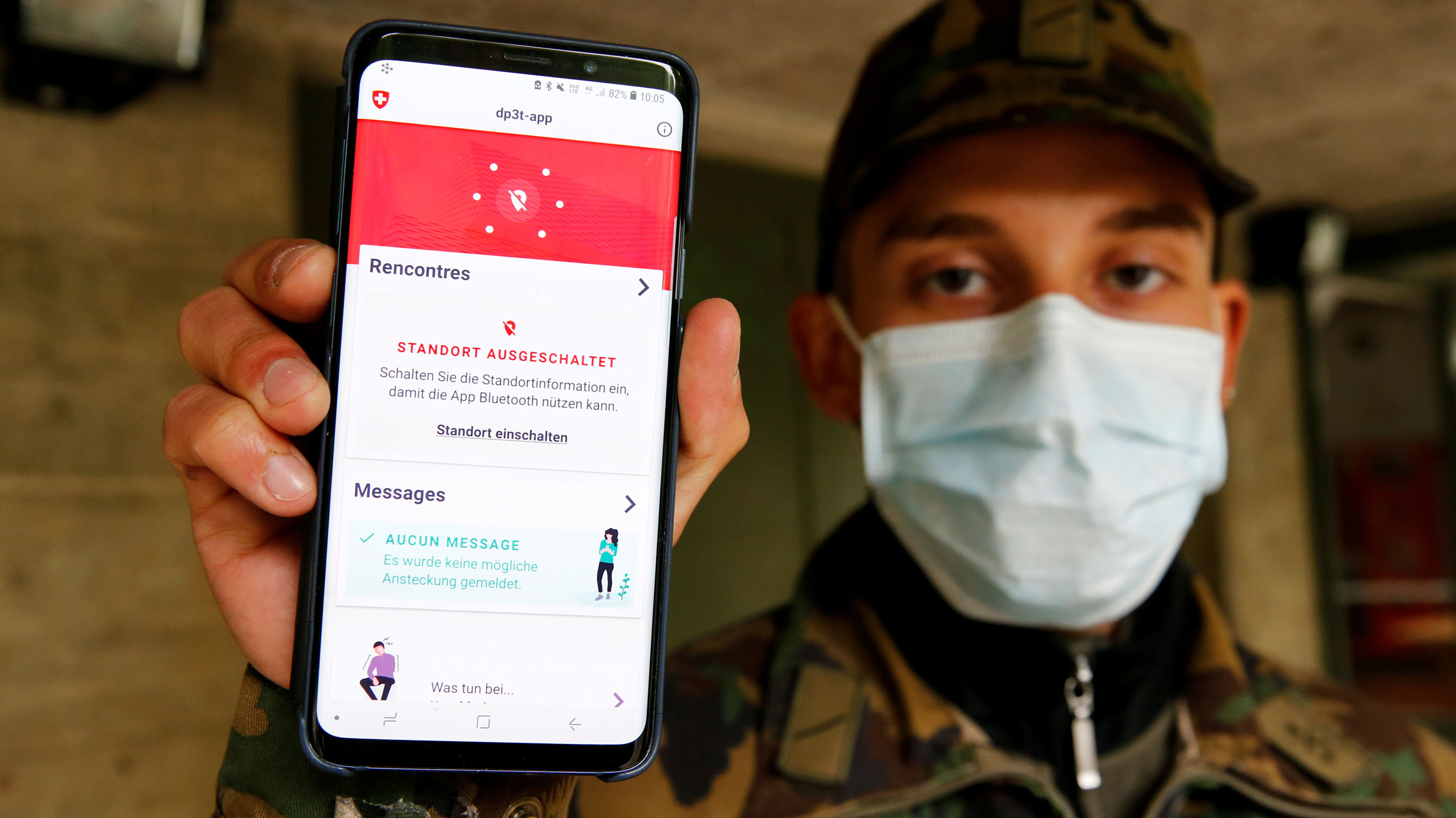 A man in fatigues and a face mask holds a phone with an app to the camera