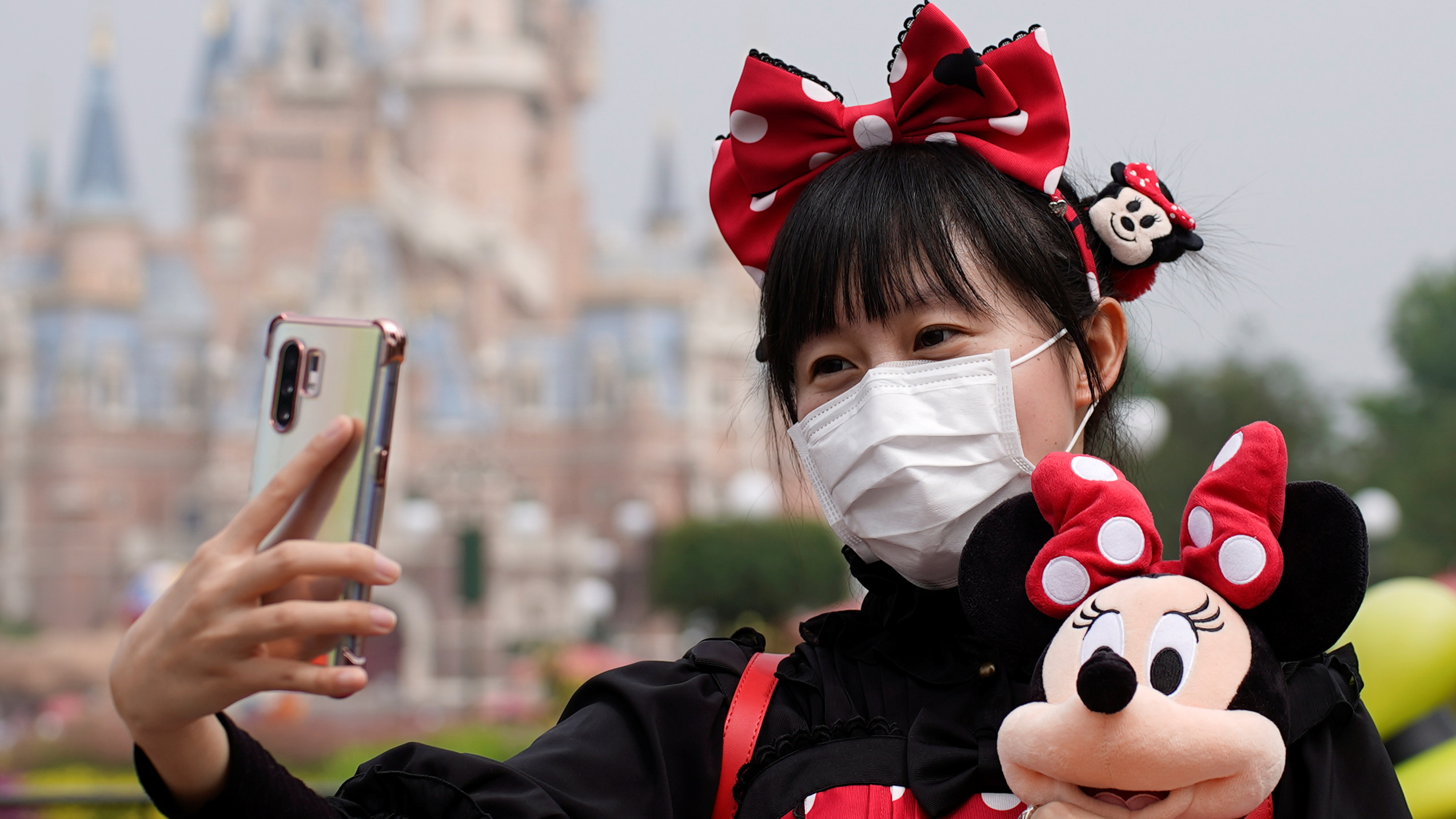 A young woman wears a red bow and holds a doll as she takes a selfie at Disneyland in Shanghai