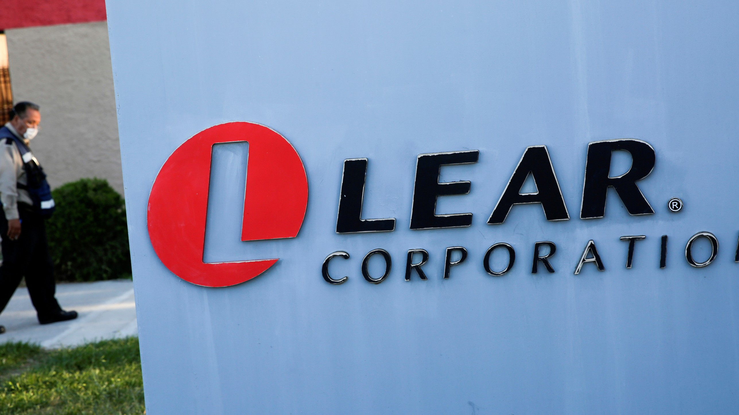 The logo of Lear Corporation, a Michigan-based car seat maker, near a man walking with a face mask