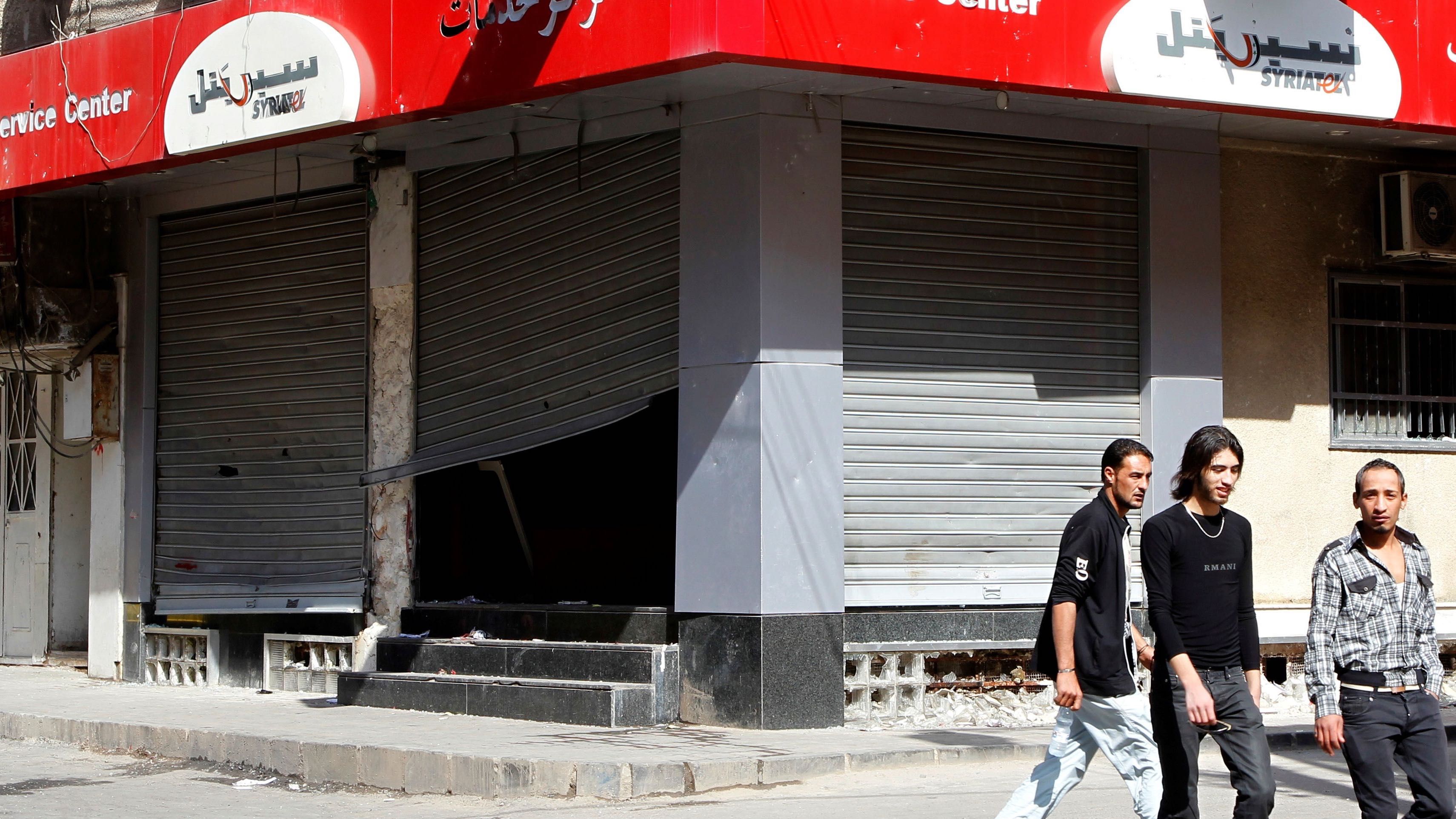 People walk past the looted premises of cellphone company Syriatel, which is owned by Rami Makhlouf, the cousin of Syria's President Bashar al-Assad, in Deraa March 21, 2011.