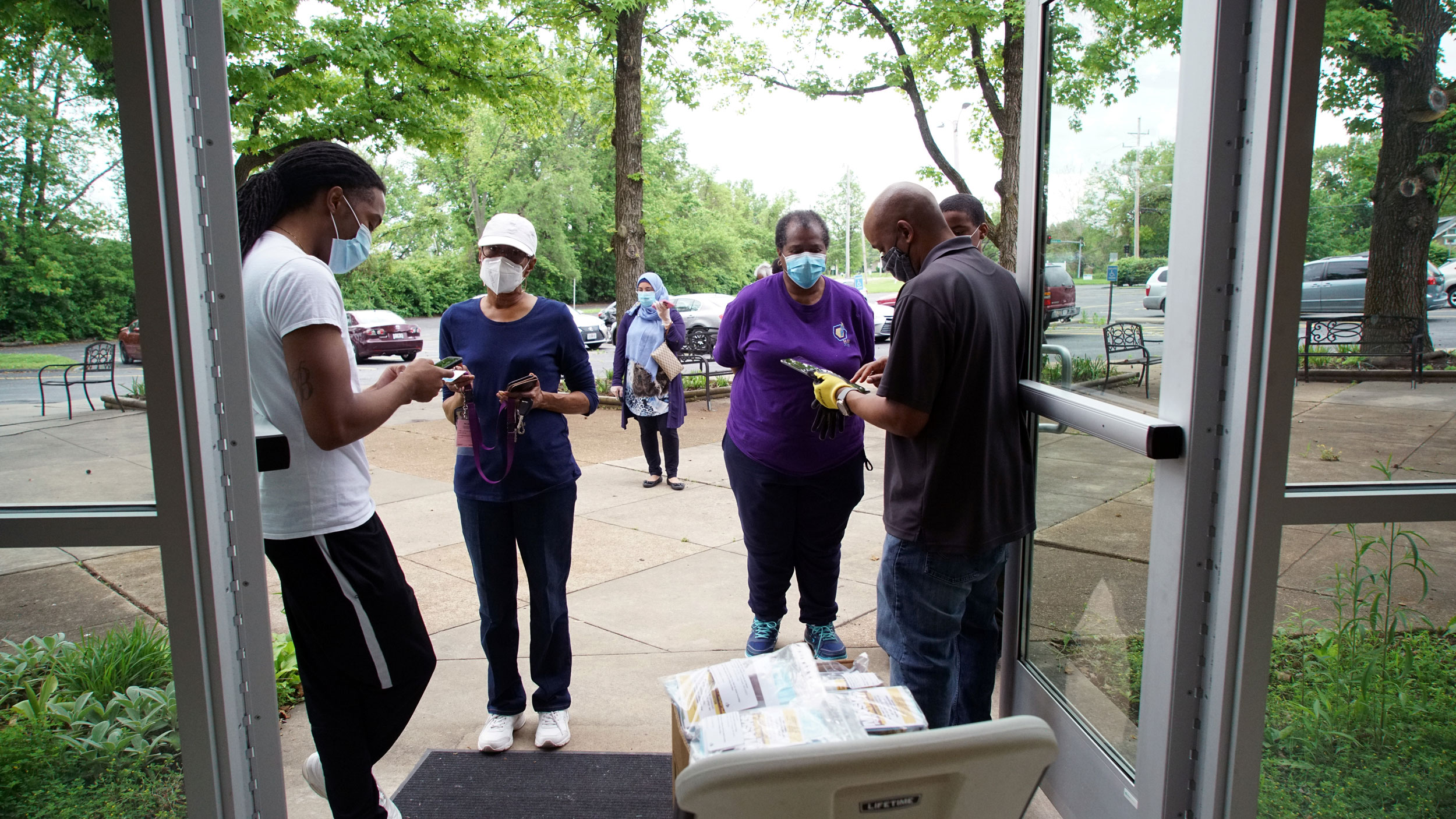 Several Black people stand around double doors in masks handing out supplies