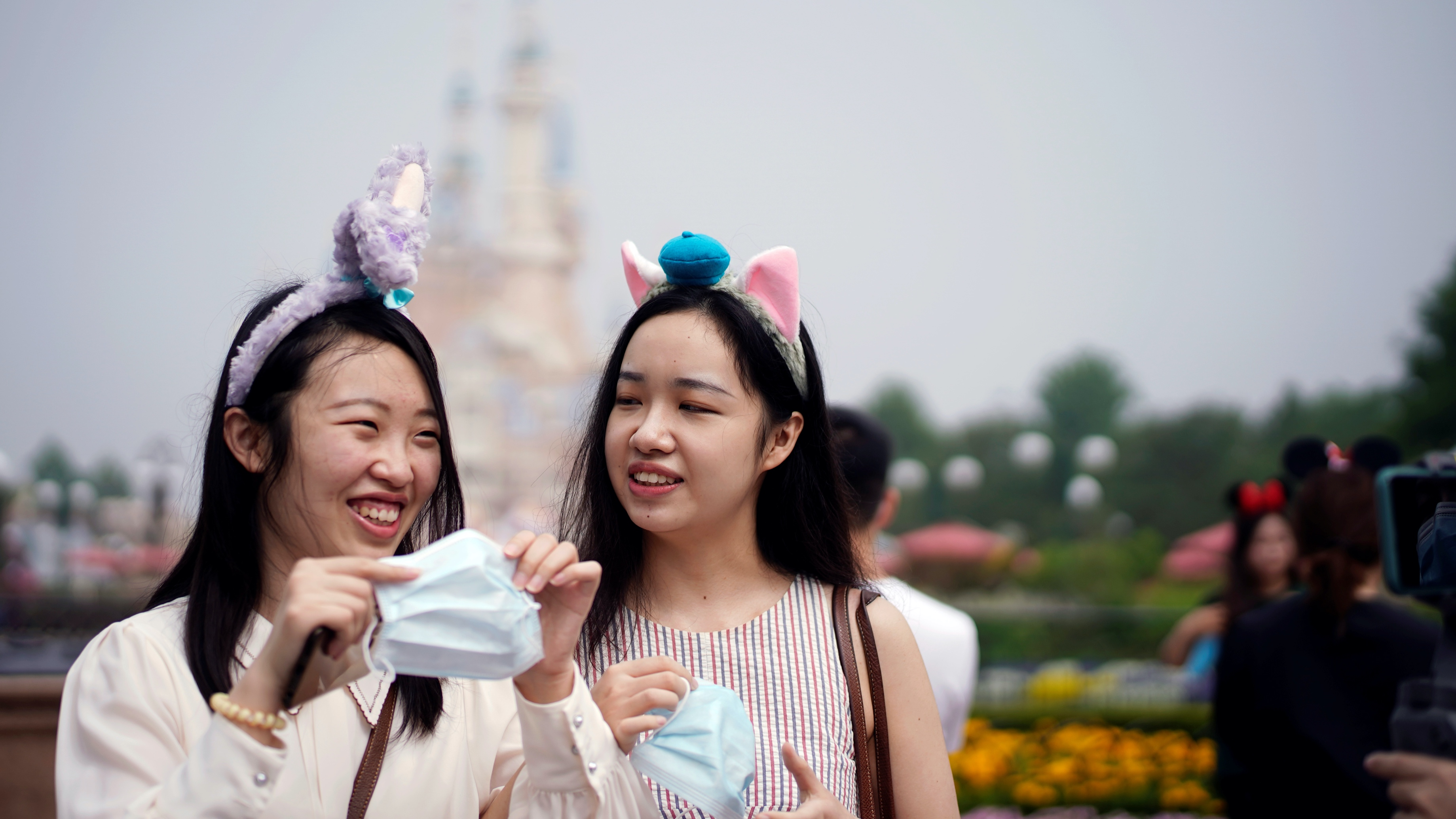 Two young women with headbands hold face masks at theShanghaiDisneyland theme park as it reopens following a shutdown due to the coronavirus disease