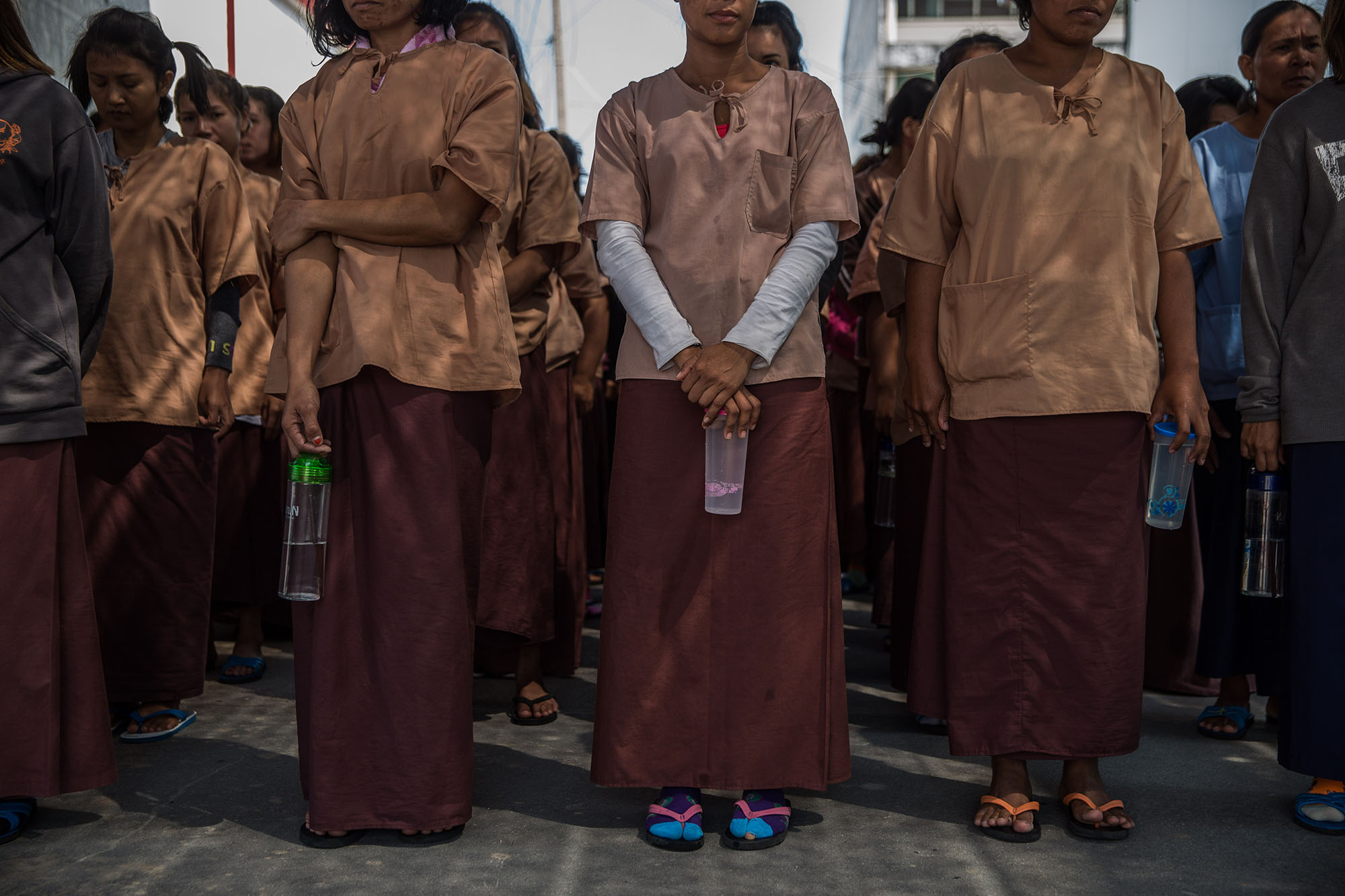 Woman stand in neat rows in a prison in Thailand.