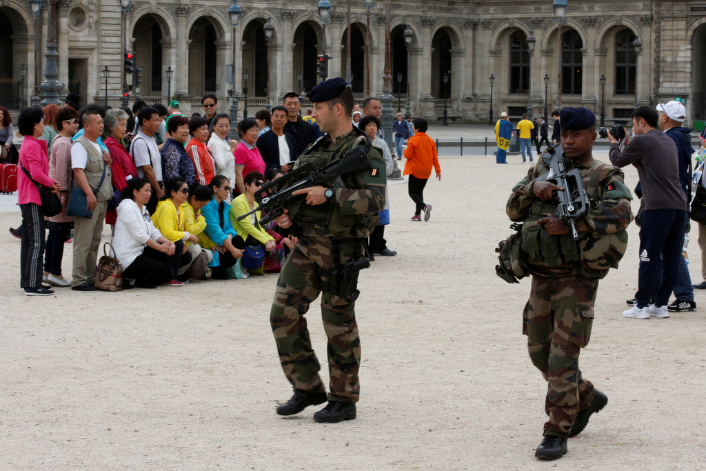 Chinese tourists take group pictures as French army soldiers patrol near the Louvre Museum Pyramid's main entrance in Paris, France, June 13, 2016 as the French capital is under high security during the UEFA 2016 European Championship.