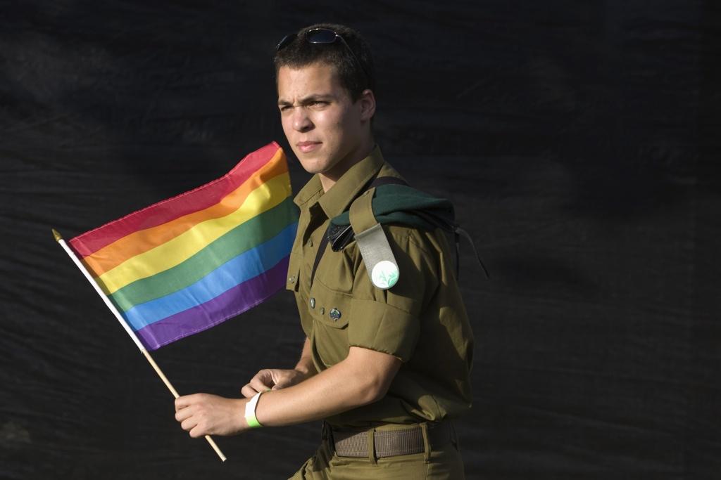 Israeli soilder holging a rainbow flag