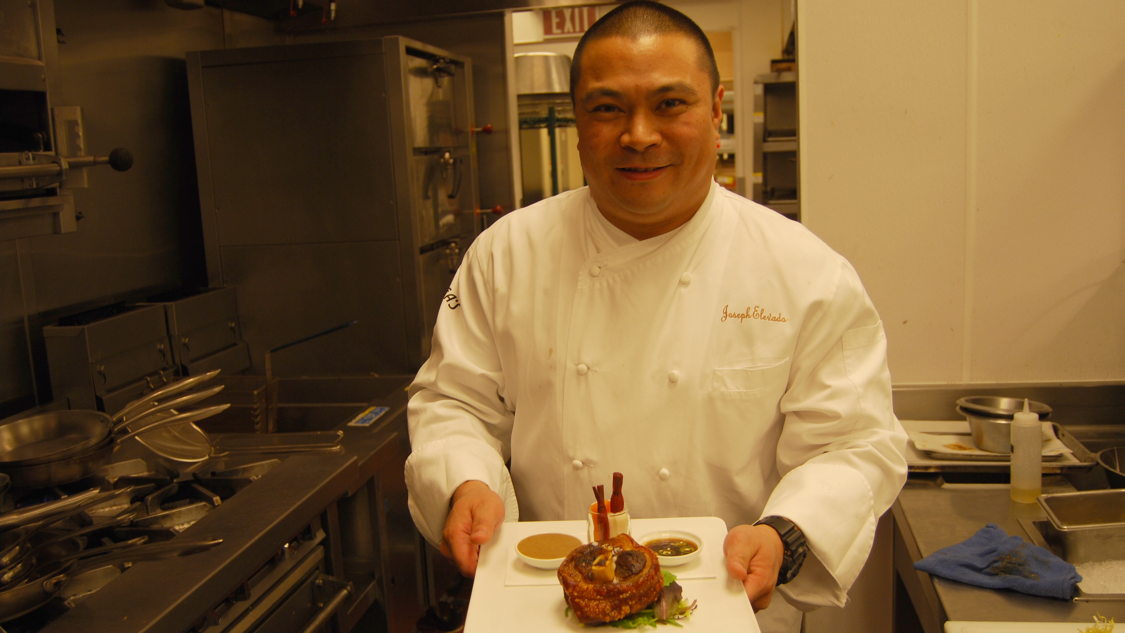 Joseph Elevado, head chef at Andrea's, holds a plate of crispy pork shank known as pata, a dish served Filipino style. His menu offers a variety of Asian dishes including Chinese, Japanese, Thai and Filipino foods.