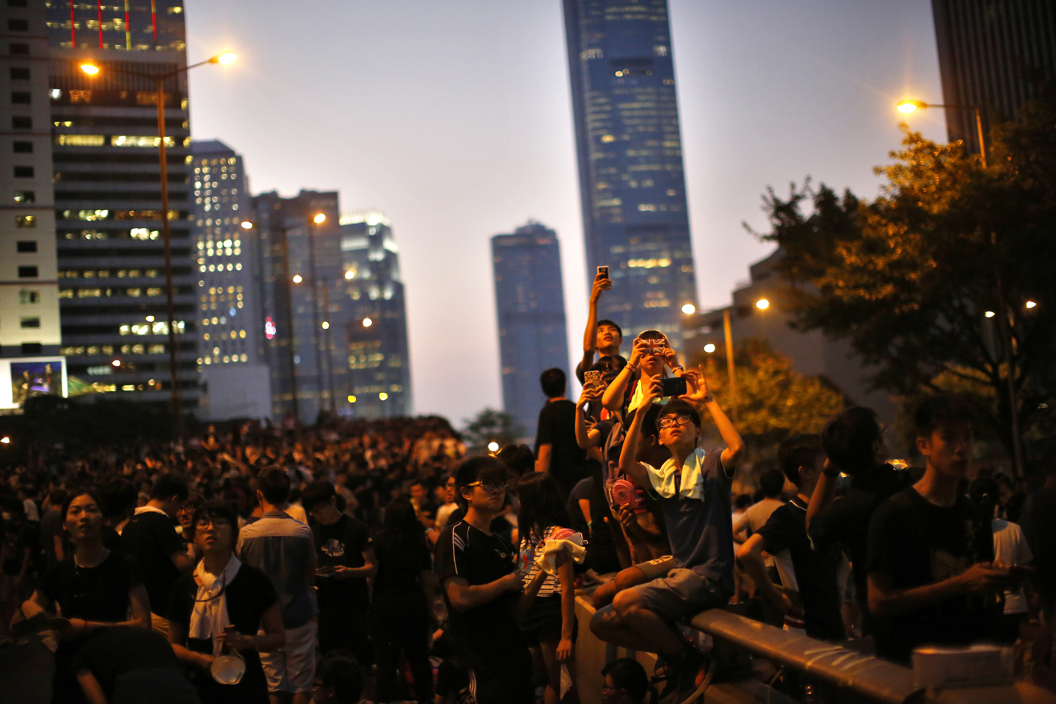 Protesters take pictures with their mobile phones as they block the main street to the financial district outside the government headquarters in Hong Kong on September 29, 2014.