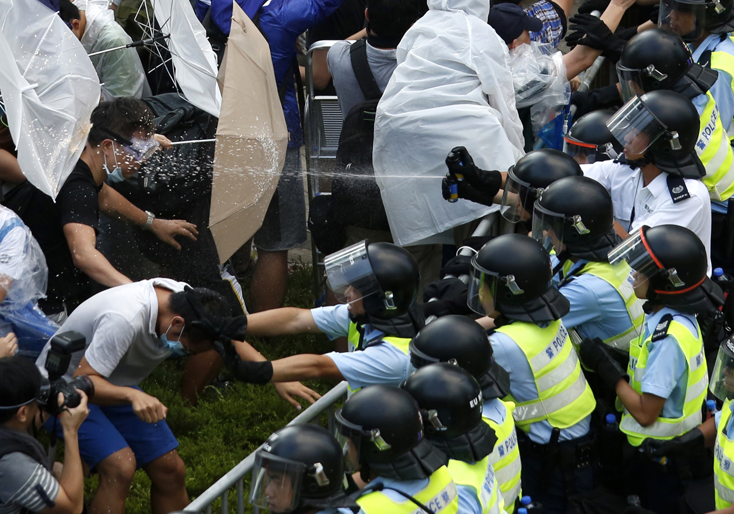 Riot police use pepper spray as they clash with protesters, as tens of thousands of protesters block the main street to the financial district outside the government headquarters in Hong Kong on September 28, 2014.