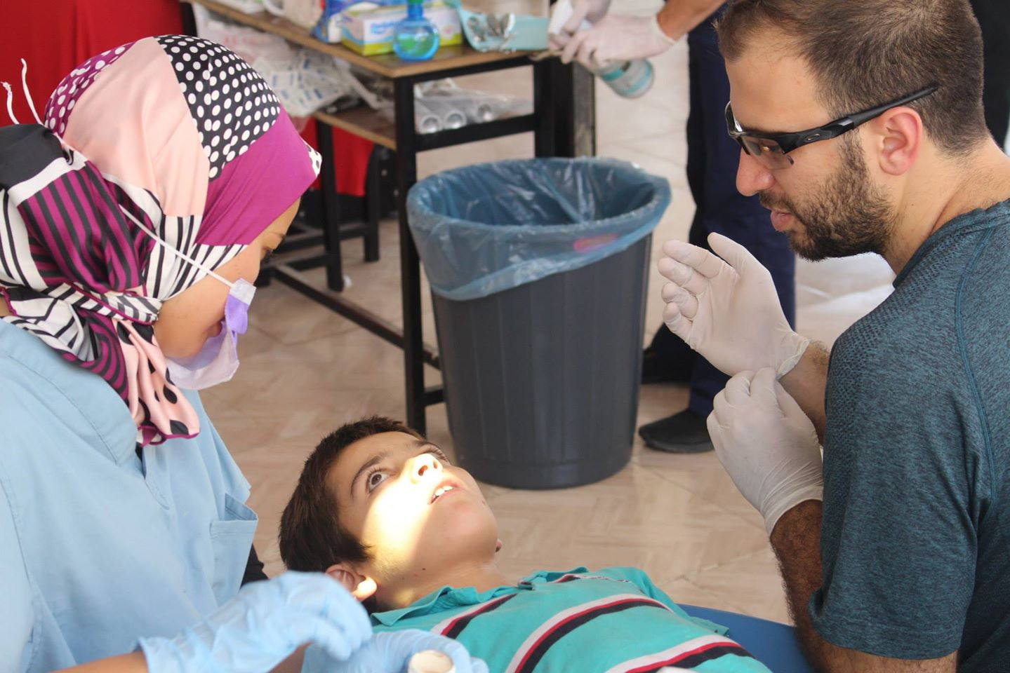 "Whether to say ""needle"" or ""sleepy juice"": Dr. Sarah Aref and Farris Barakat help a Syrian boy at the temporary Syrian American Medical Society dental clinic on the Turkish-Syrian border."