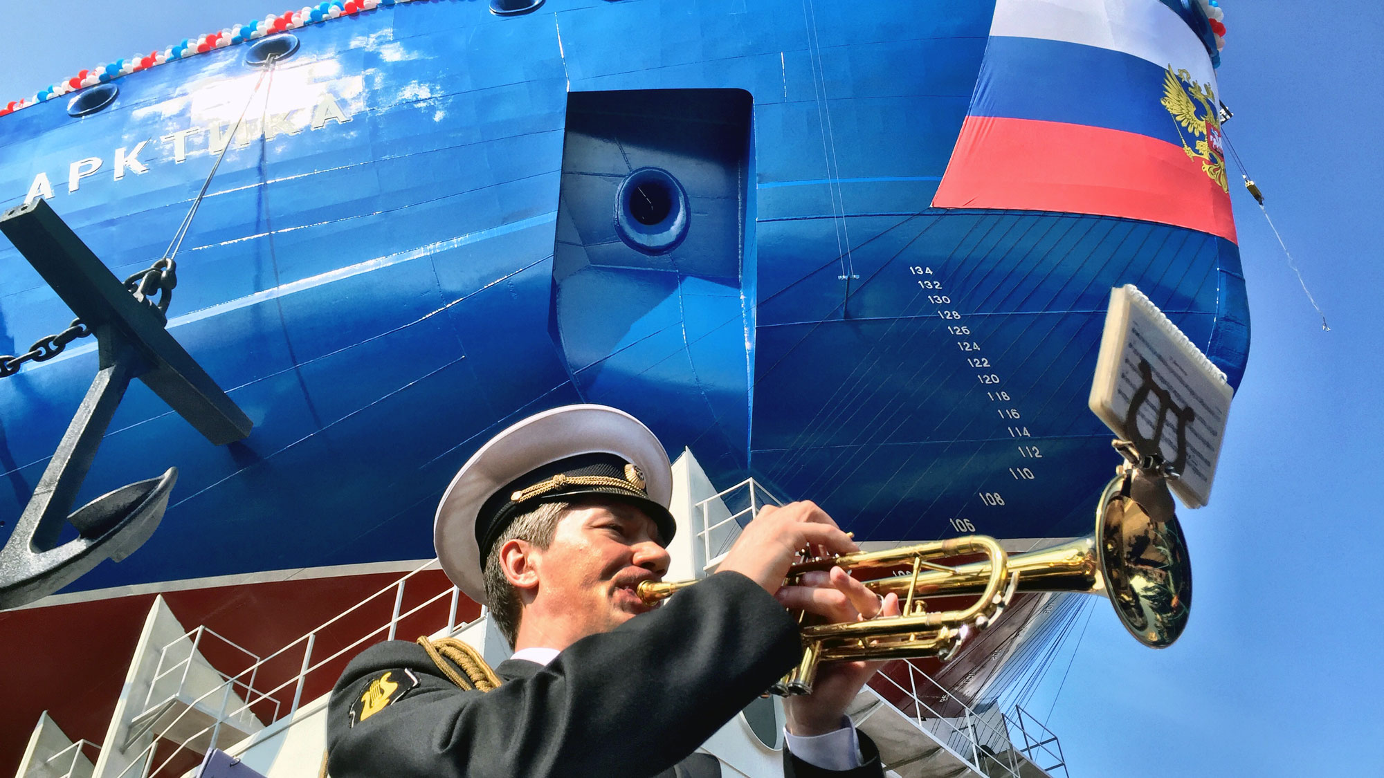 A man in a military uniform plays the trumpet. Behind him is the blue hull of the icebreaker ship Arktika.