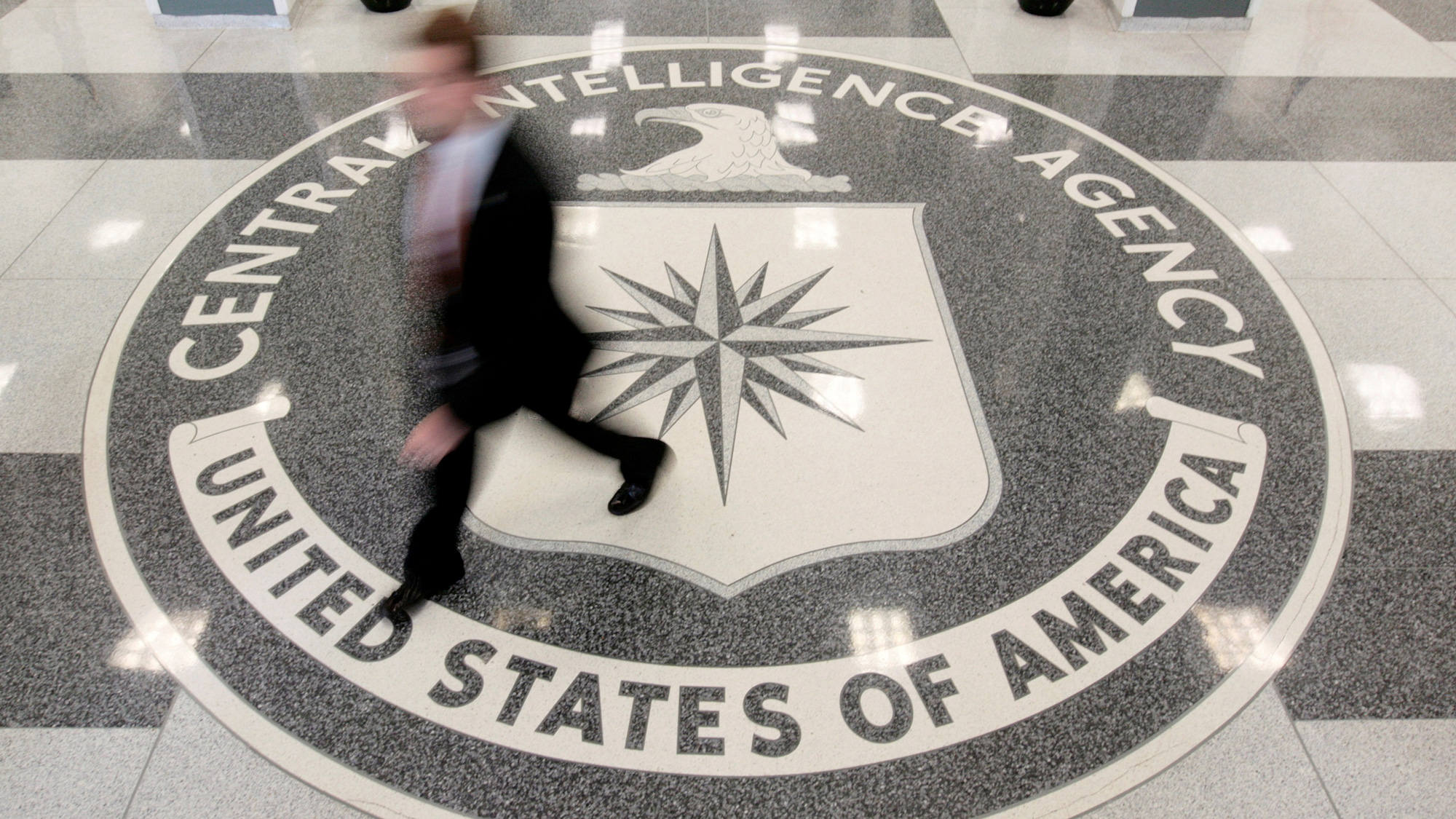 A man's image is blurred as he walks across a giant marble seal in the floor of the CIA headquarters in Langley, Virginia.