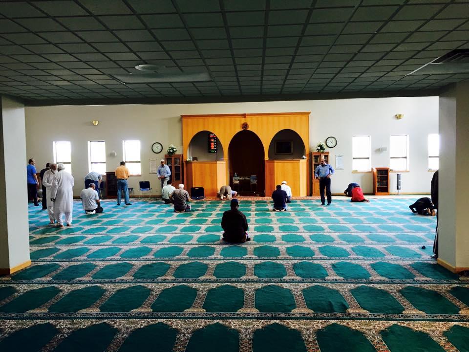 A few men pray in an open room
