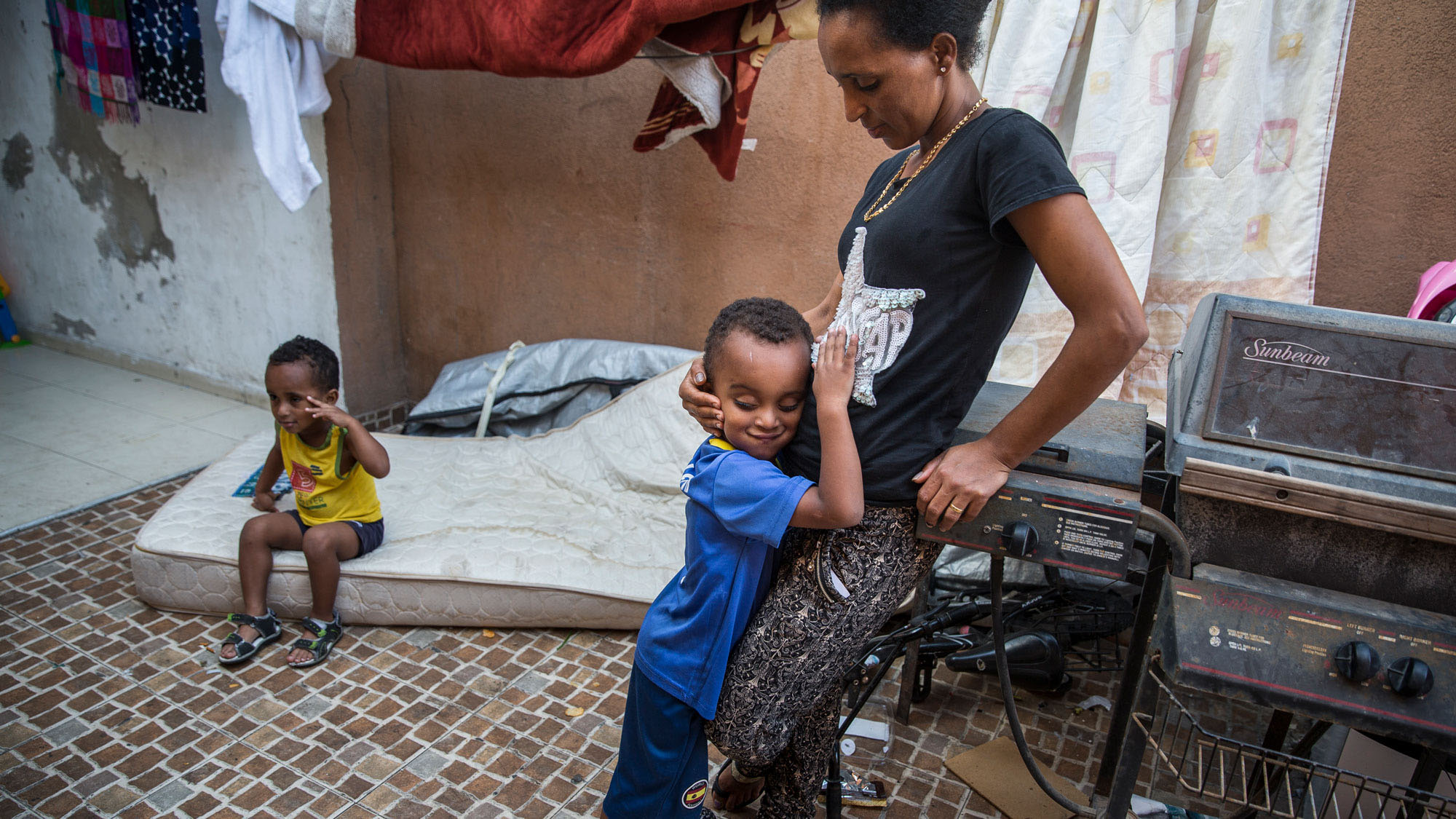 Brkitay Gebru with her sons, Tariki, 4, and Natanael, 3, in the courtyard of their building where immigrants from Eritrea and other countries rent rooms in Tel Aviv.