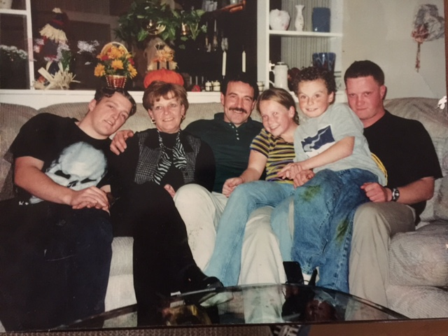 Family of six sitting closely together on a sofa
