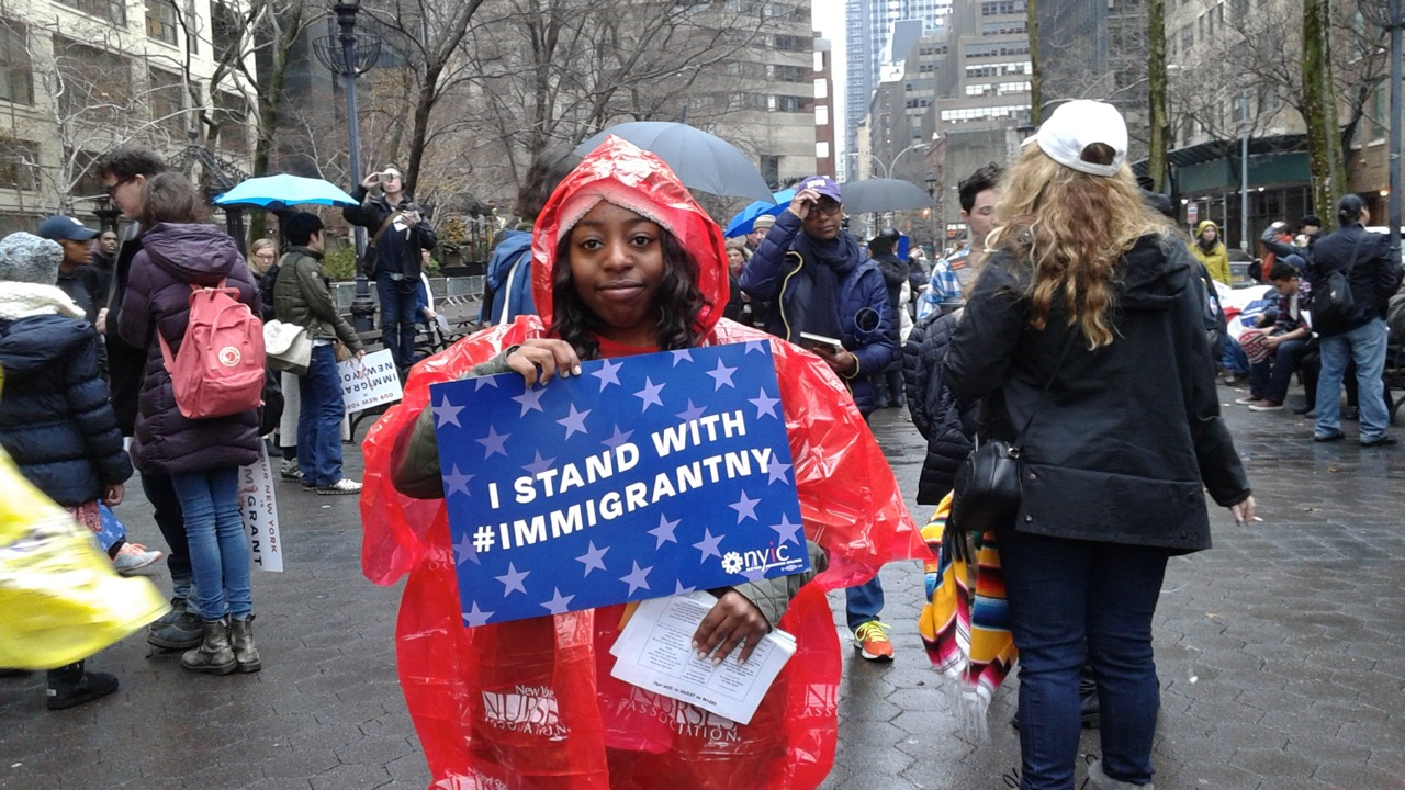 """Woman in rain parka holding sign that reads """"I STAND WITH #IMMIGRANTNYC"""""""