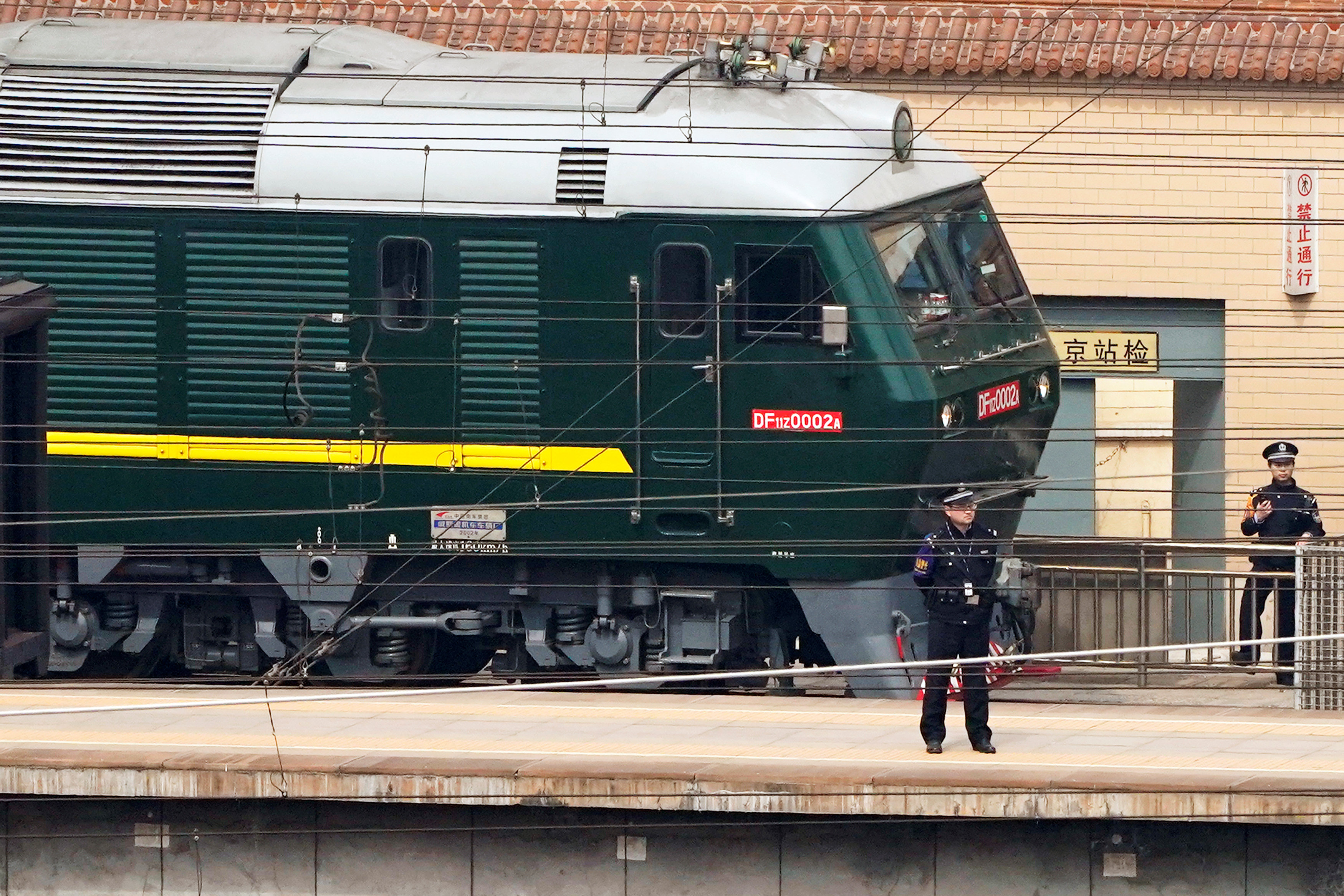 Police officers keep watch next to a train, believed to have carried a North Korean delegation to China