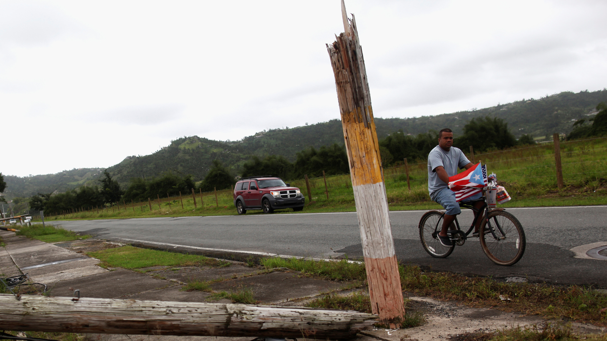 A man rides a bicycle past a collapsed utility pole after Hurricane Maria hit the island in September 2017.