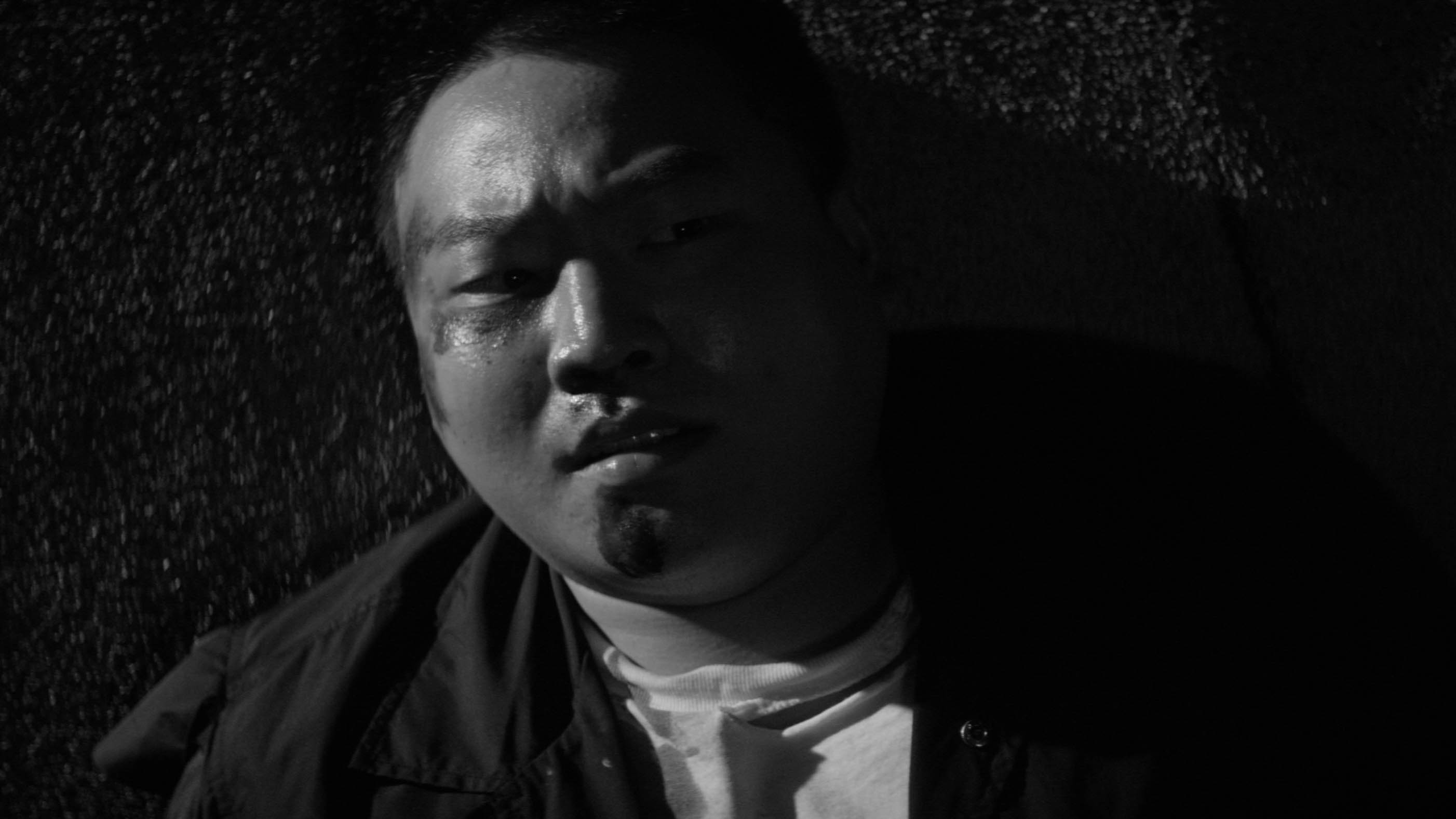 Man with beaten face on pavement, black and white still