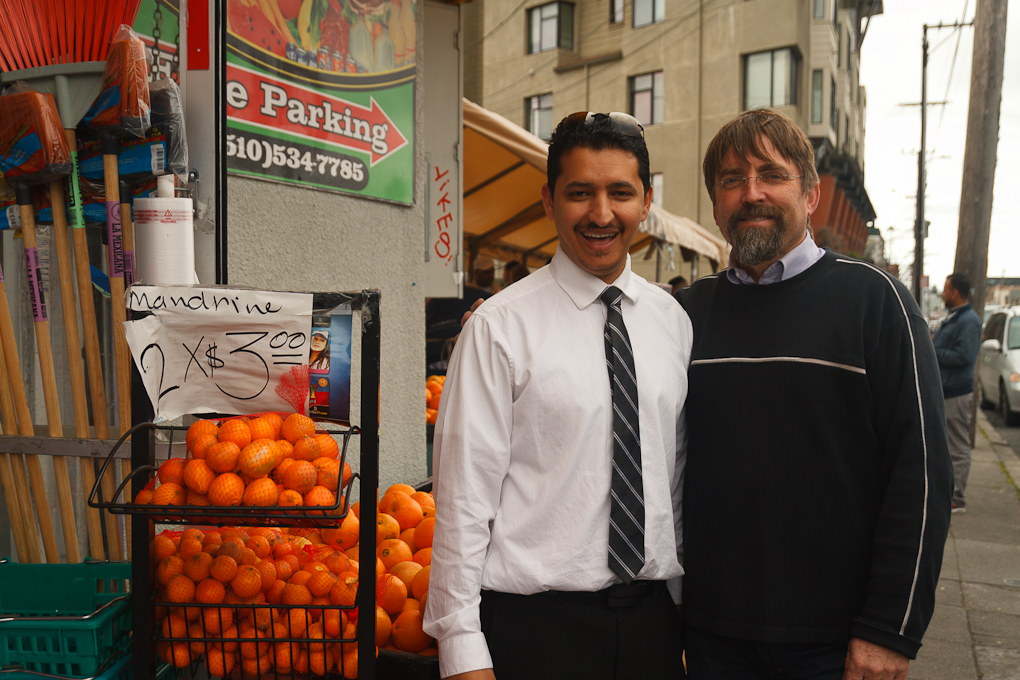 Two men in smile in posed photo in front of small market