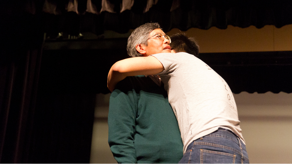 A man is hugged by a young man on stage