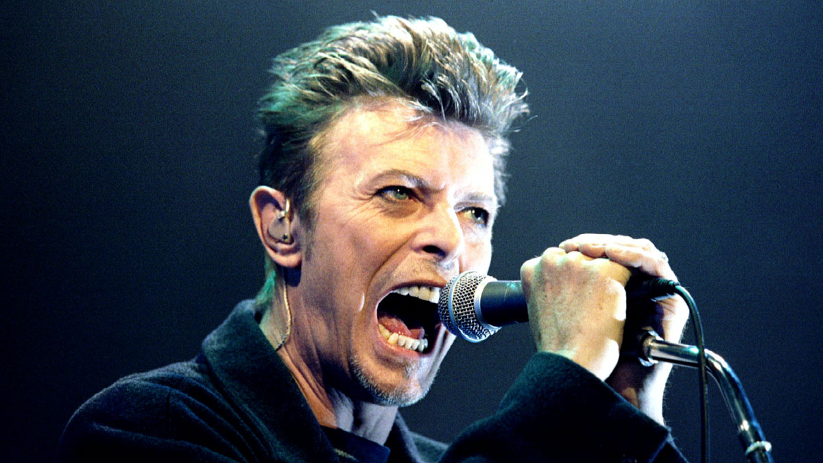 British Pop Star David Bowie screams into the microphone as he performs on stage during his concert in Vienna February 4, 1996.