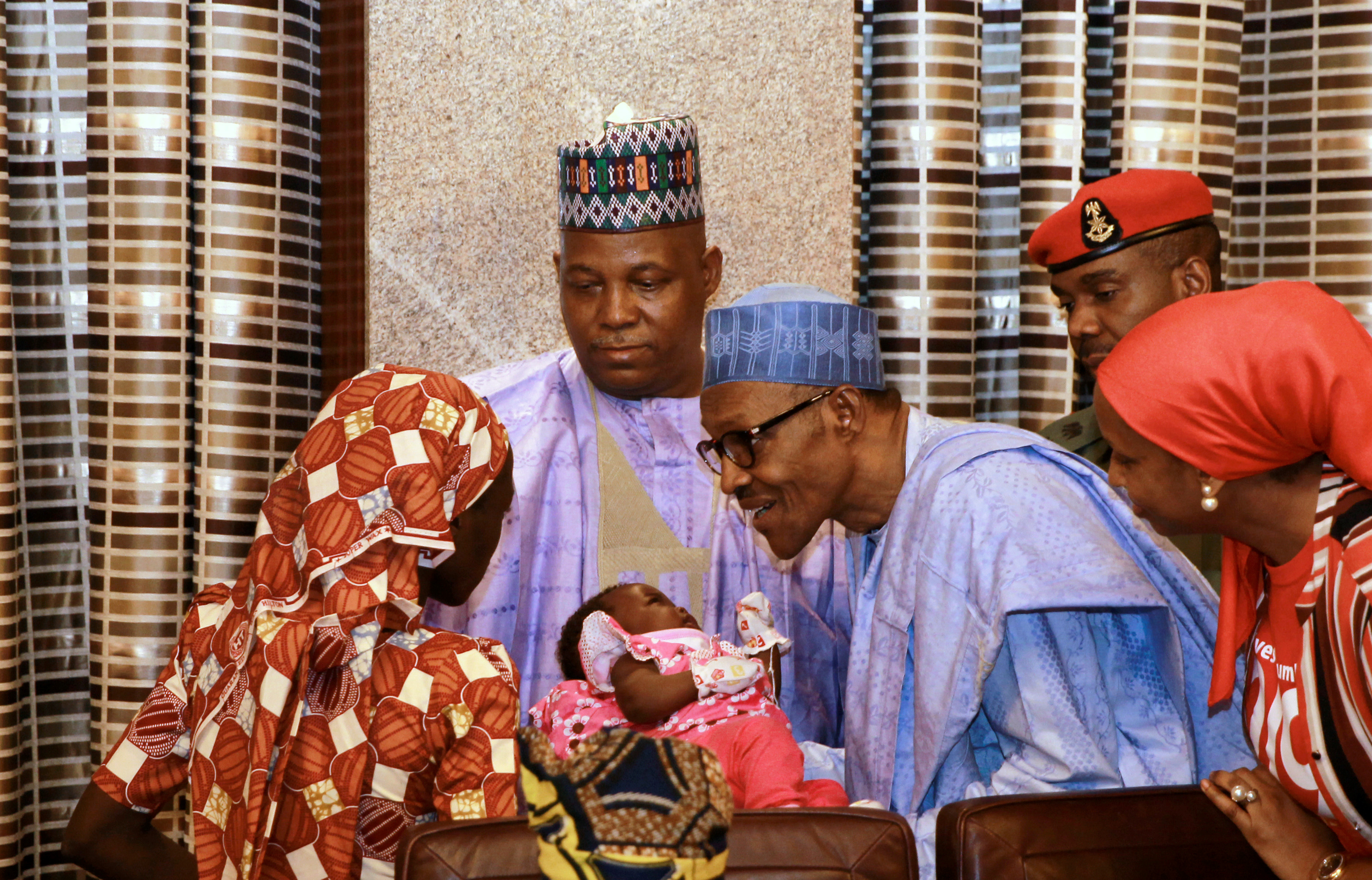 Amina Ali Darsha Nkeki, a Nigerian schoolgirl rescued after over two years of captivity with Boko Haram militants, presents her child to President Muhammadu Buhari in Abuja, Nigeria May 19, 2016.
