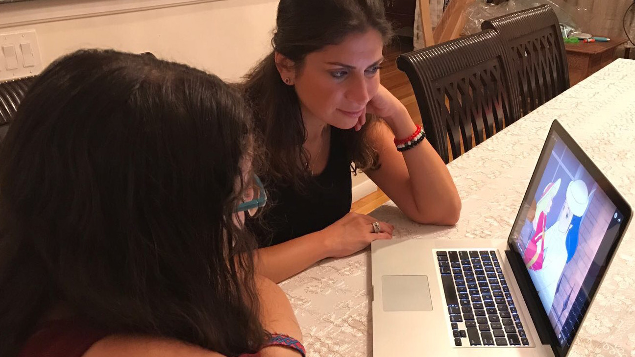 Dima Basha (right) watches dubbed cartoons with her daughter, Angelina, to help her learn formal Arabic.