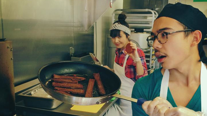 """Kale Walch cooks a pan of """"bacon,"""" one of the meatless meats that he and his sister Aubry Walch (in the back) whip up for The Herbivorous Butcher. They're hoping to open what they say is the world's first vegan butcher shop in the spring."""