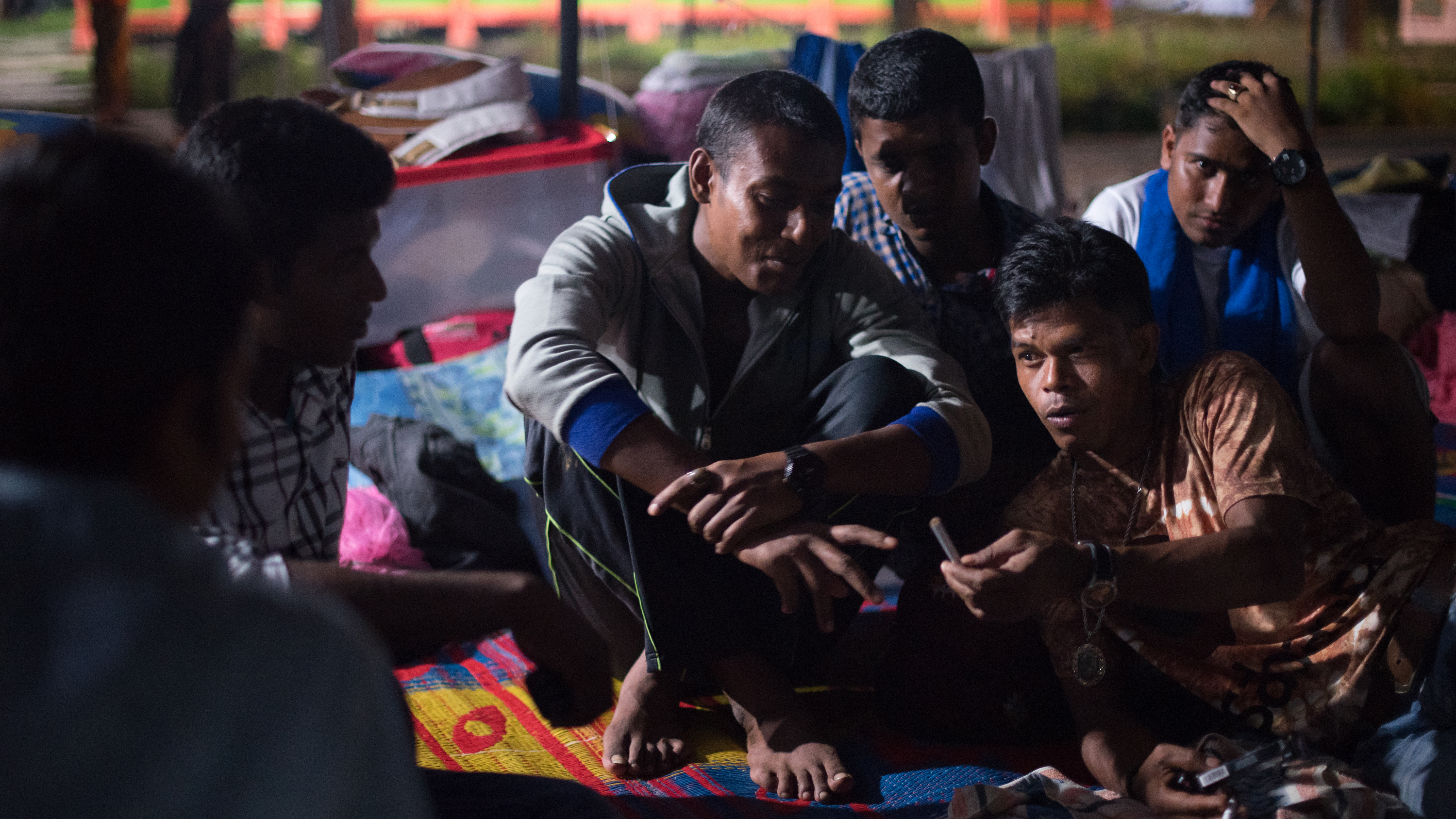 Taufik (bottom right) is a fisherman who saved the Rohingya and Bangladeshi from sea in May. Even though they aren't real family, he says, he loves them and he feels a responsibility to take care of them. He visits the Bayeun, East Aceh, Indonesia refugee