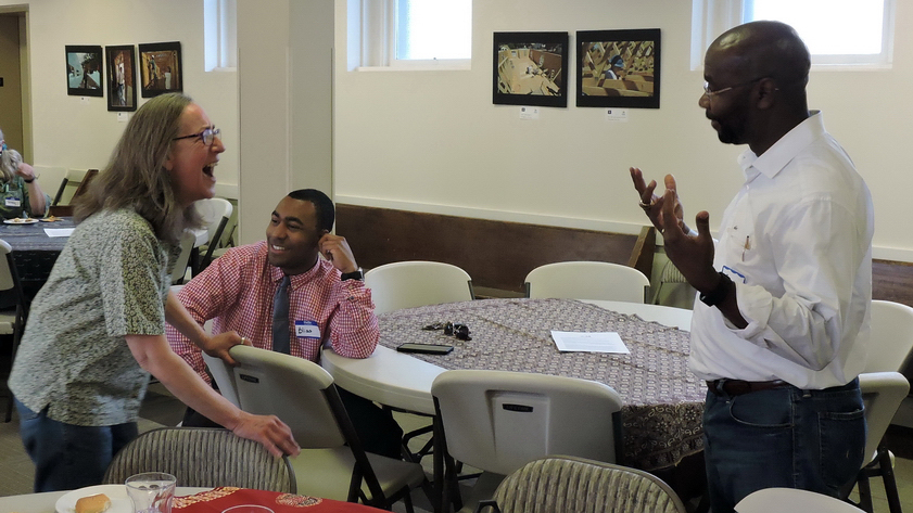 Wilmot Collins gestures across table to a woman who he is speaking with