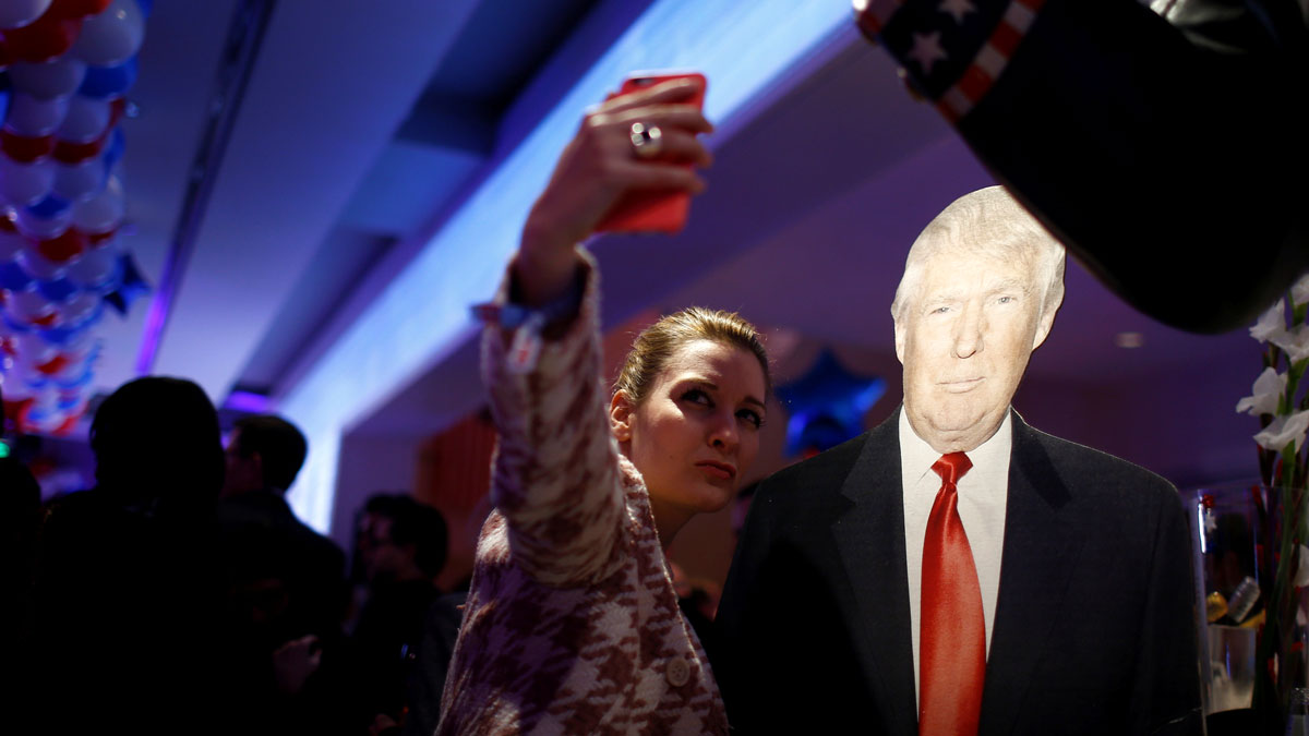 A woman photographs herself with a cardboard figure of U.S. Republican presidential candidate Donald Trump in Berlin, Germany, November 8, 2016. REUTERS/Axel Schmidt