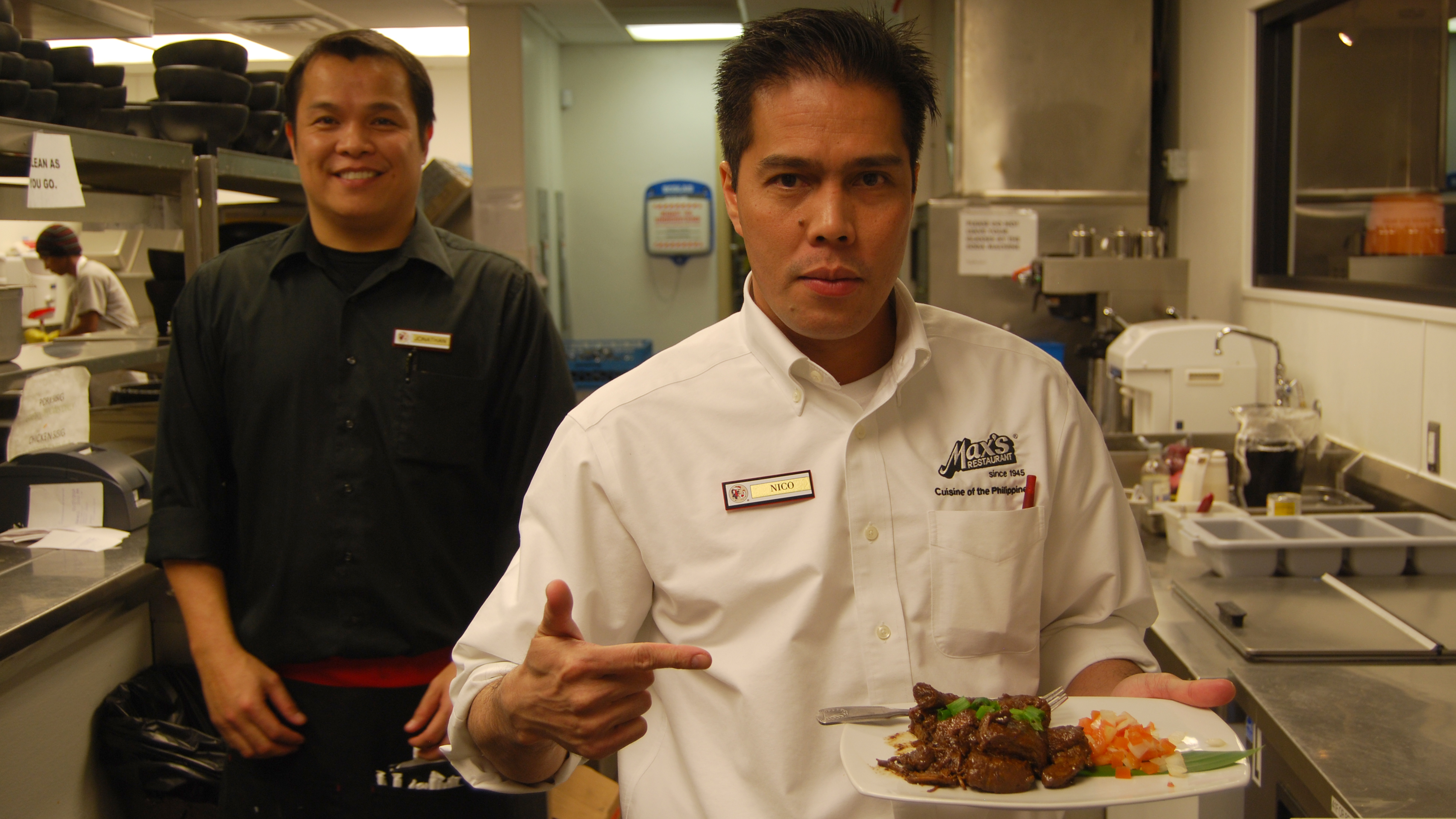 Nico Vidal, manager at the new Las Vegas Max's, a well-known Philippine chain that's opening new locations in the US and Canada. Vidal is holding a plate of Pinatuyong Pork Adobo.