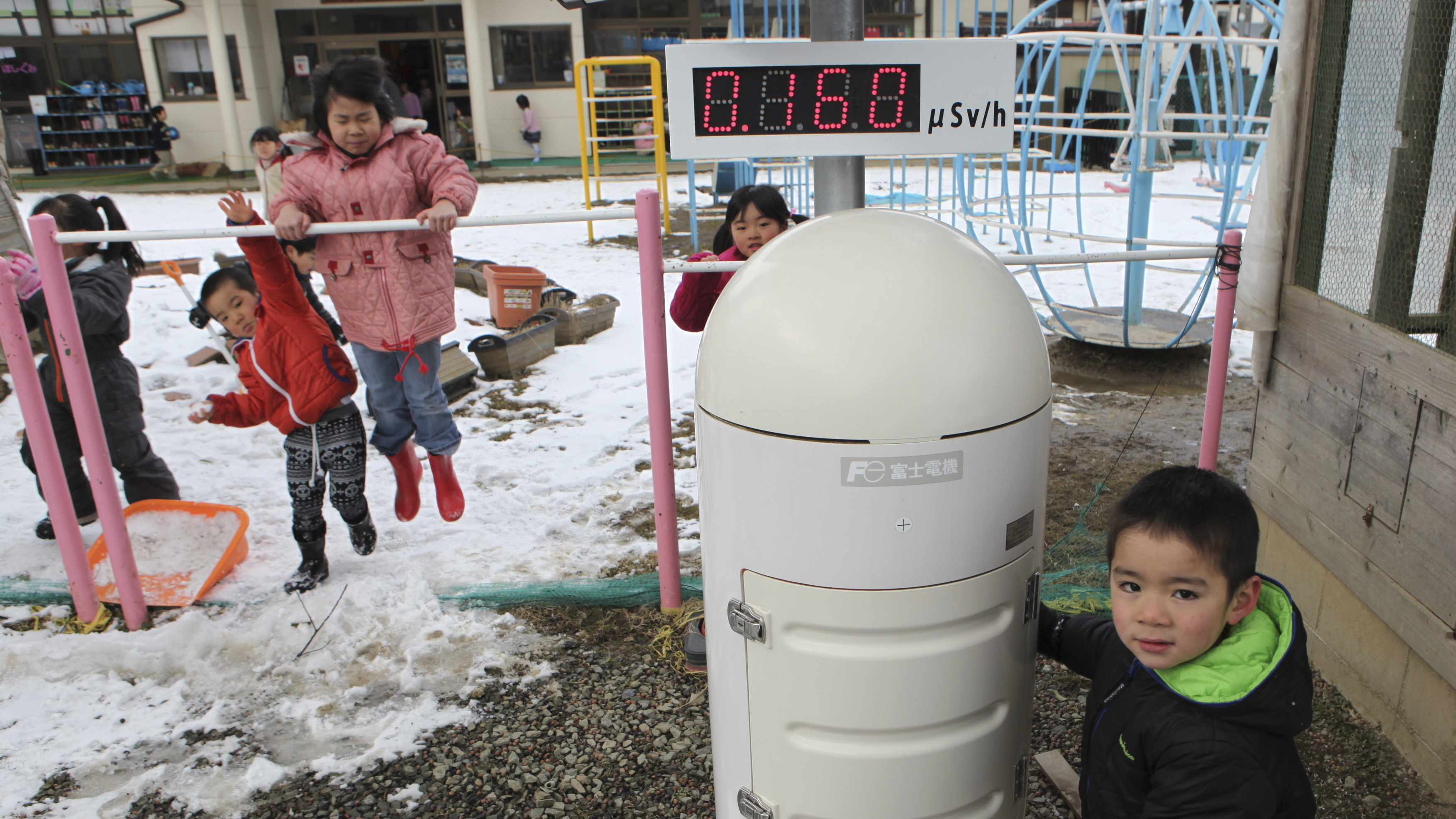 Children play near a Geiger counter that monitors radiation at a kindergarten about 30 miles from the tsunami-crippled Fukushima Daiichi nuclear power plant. The government is increasingly pushing families displaced by the disaster to return to their home